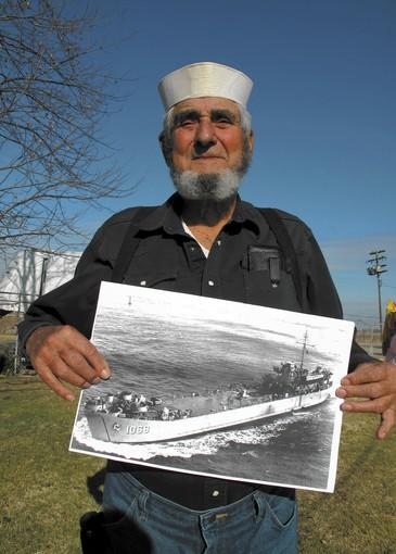 Wearing his original Navy white uniform cap, Norman D. James, 81, who served as a gunner's mate on the USS Orange County, displays a photograph of the ship as he stands in the front yard of his farmhouse near Sacramento.