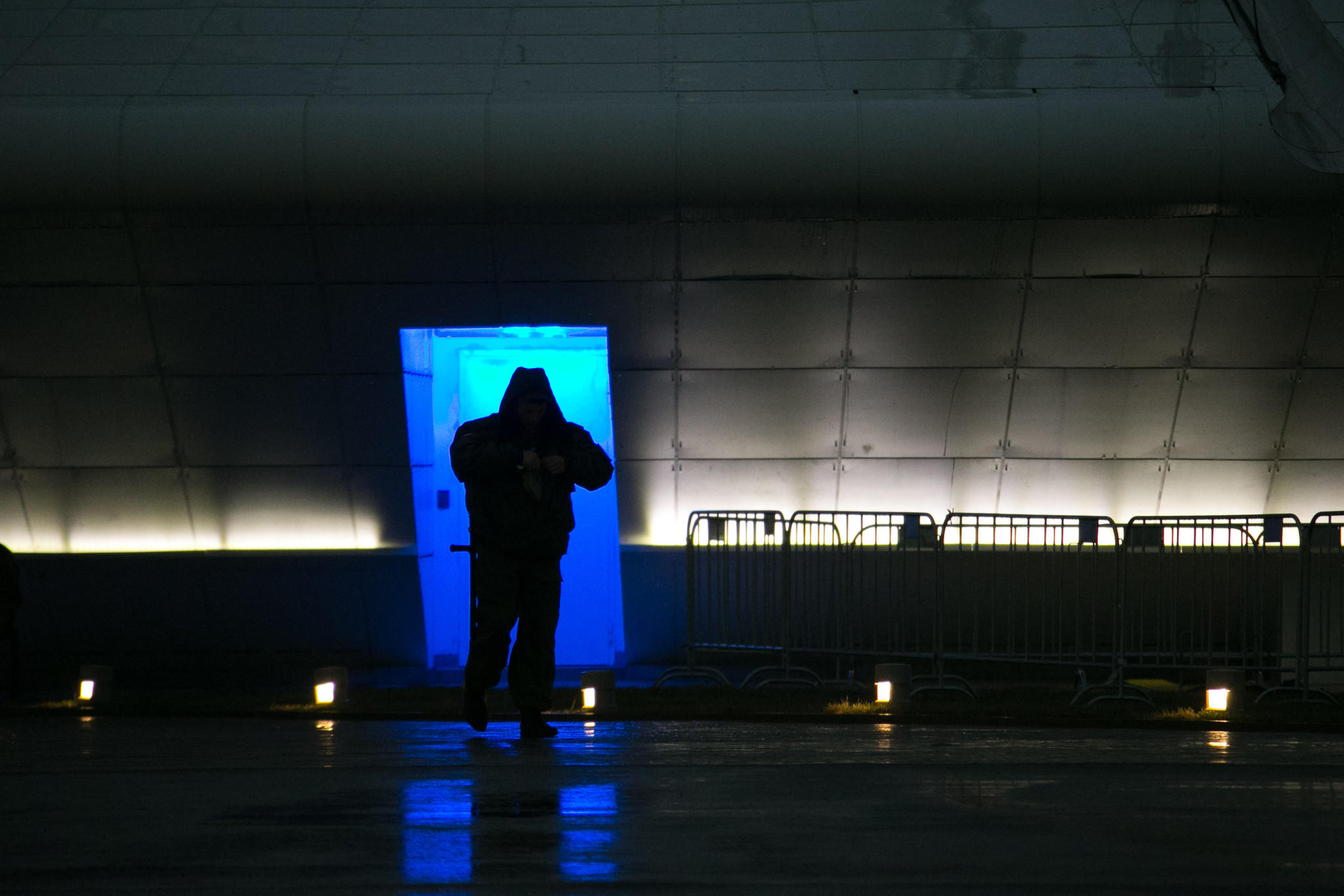 A security guard is silhouetted at the base of the Olympic Cauldron in Olympic Park prior to the 2014 Sochi Winter Olympic Games.