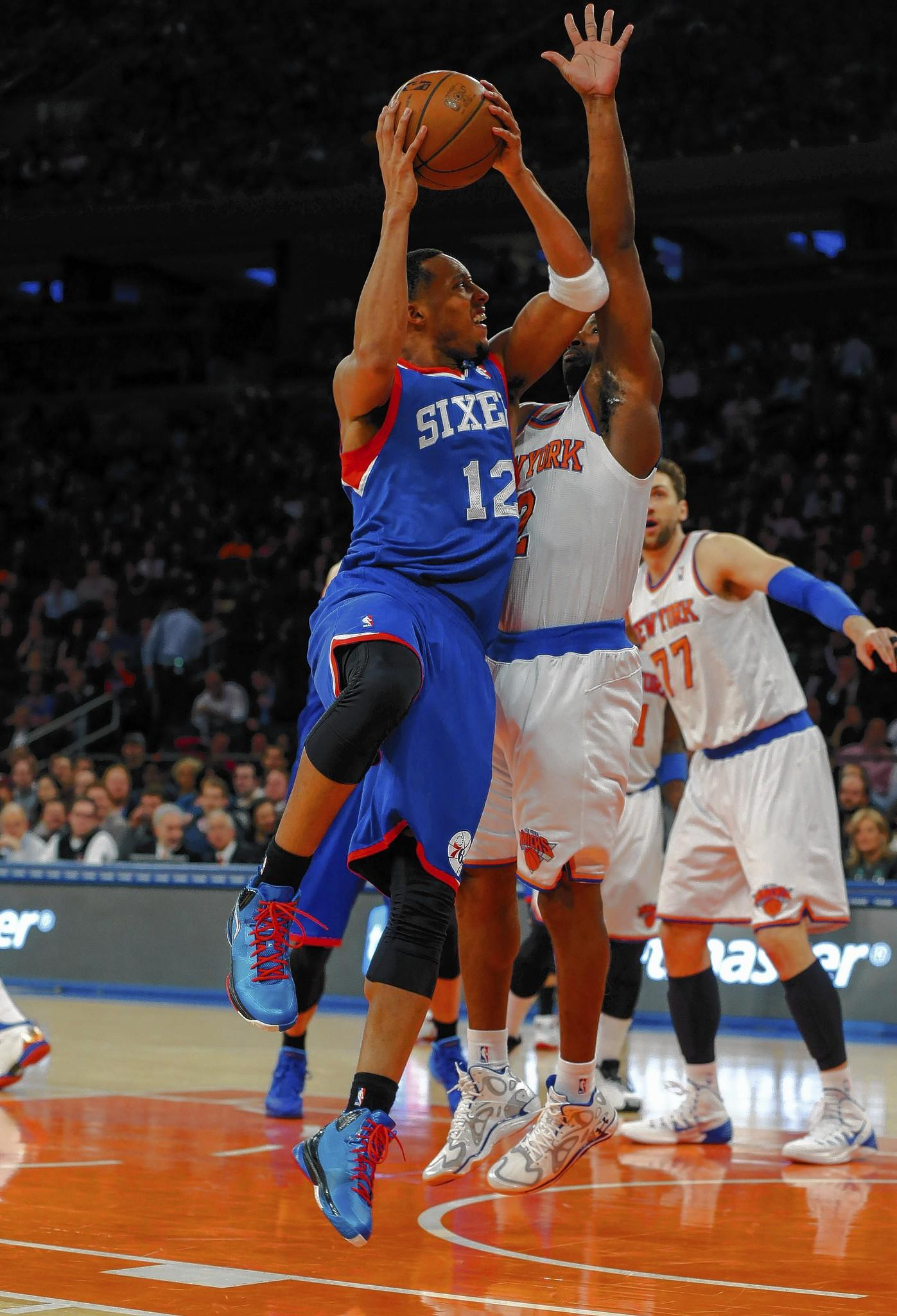 Jan 22, 2014; New York, NY, USA; Philadelphia 76ers small forward Evan Turner (12) drives to the basket during the first half against New York Knicks point guard Raymond Felton (2) at Madison Square Garden.