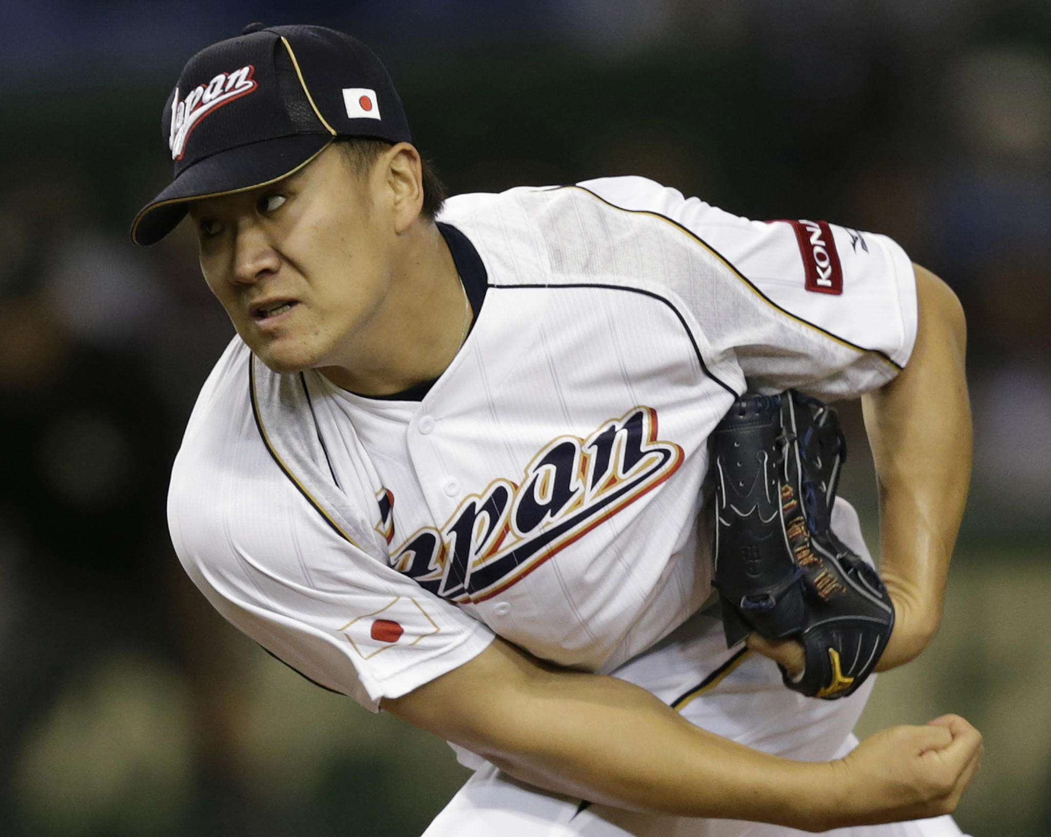 Japan's pitcher Masahiro Tanaka pitches against the Netherlands in the fifth inning at the World Baseball Classic (WBC) second round game in Tokyo in this March 12, 2013 file photo. Tanaka and the New York Yankees agreed to a seven-year, $155 million contract. The 25-year-old right-hander narrowed his choice to the Yankees and Los Angeles Dodgers, who were offering more overall money but not an opt-out clause. His contract with the Yankees includes an escape clause after four years. Picture taken March 12, 2013.