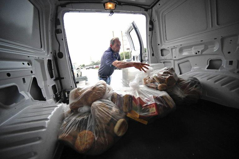 Boca Helping Hands driver Pete Rather who started as a volunteer, loads donated food from area restaurants and supermarkets.