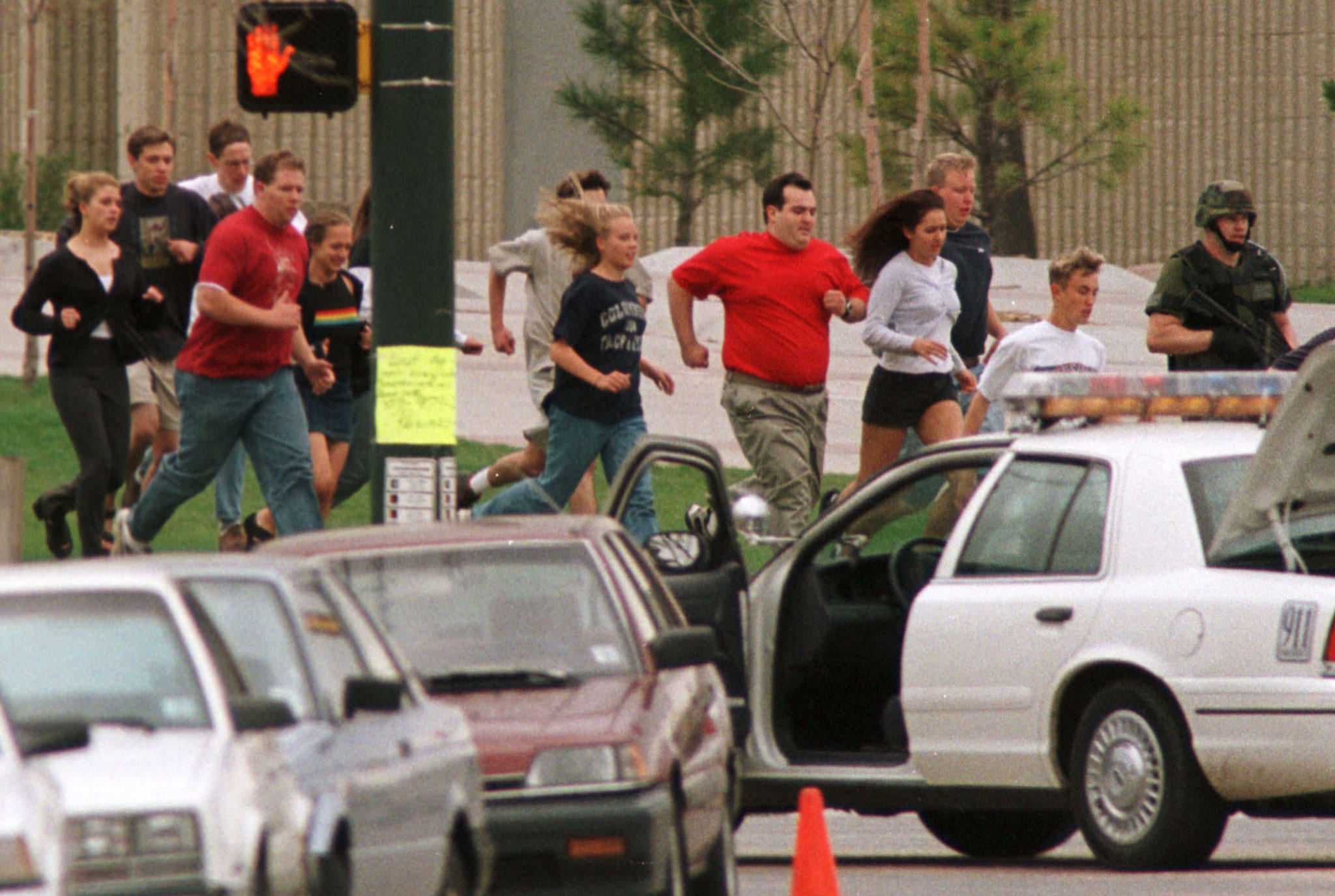 Columbine high school students run from the school after gunmen opened fire on terrified students, killing up to 25 people before taking their own lives on April 20, 1999 police said.