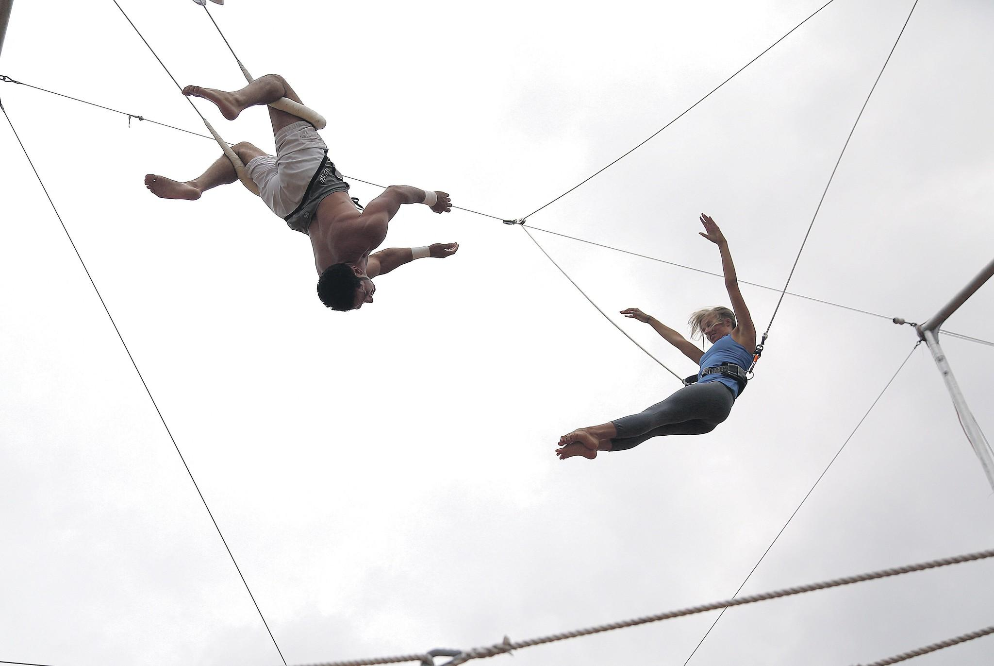 Lake Worth Circus Experience instructor Andres Leon, left, works with student Mary Mankamyer, 27, of Wellington on the trapeze. The Lake Worth company gives anyone the opportunity to learn tricks, without running away with the circus.