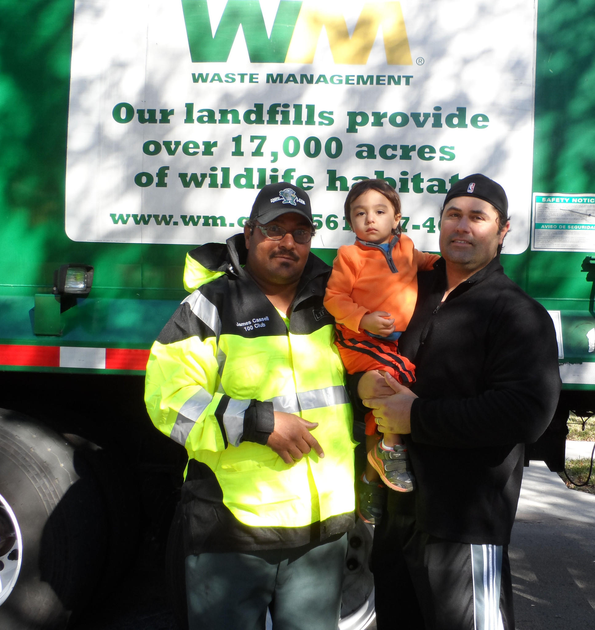 Waste Management driver James Cassell, left, visits with Mason Tracy, 2, and his dad James following his actions last week to rescue Mason from traffic at his neighborhood intersection in Delray Lakes.