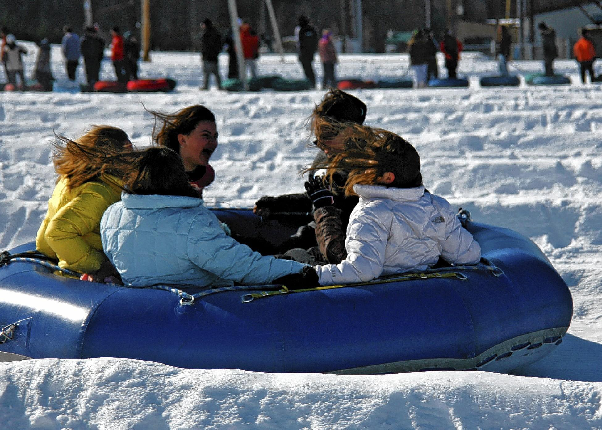 A close up of a family snow tubing at Blue Mountain near Paklmerton.