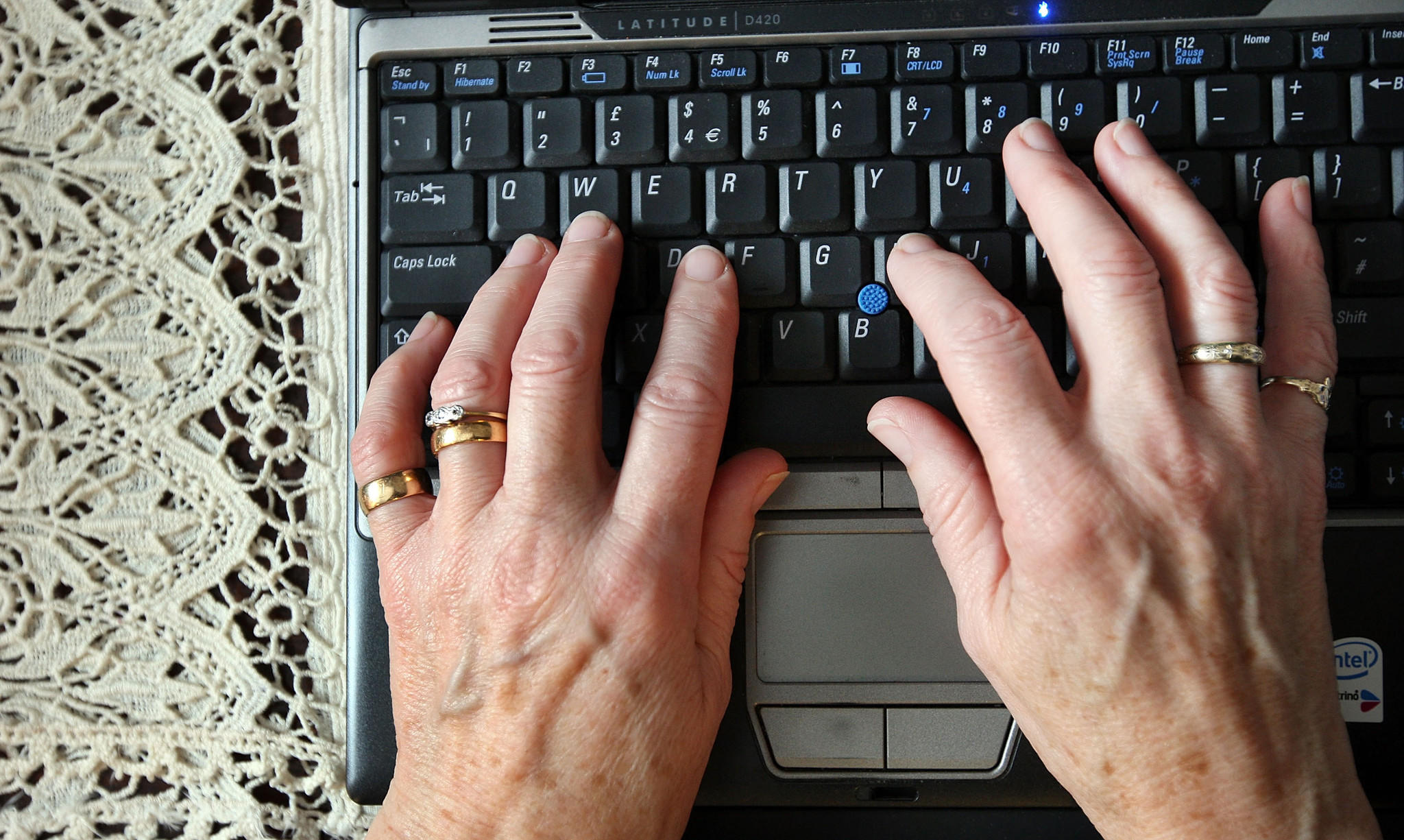 A woman checks her social networking accounting on a laptop computer.