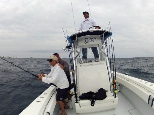 Capt. Mark Lamb of Doing It All watches from the tower as Lloyd Waters fights a sailfish while receiving encouragement from Daryl Deka.