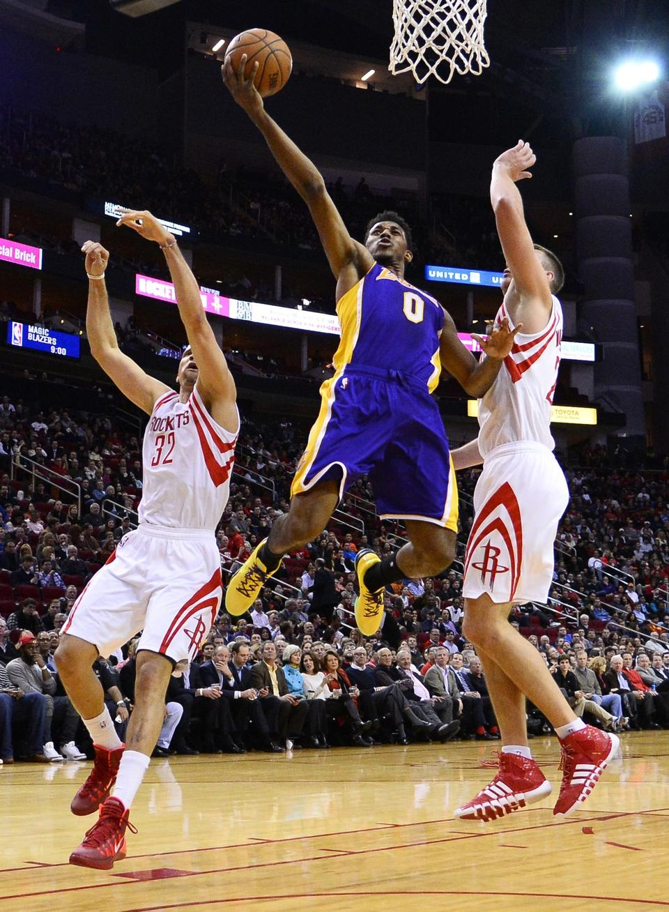 Lakers small forward Nick Young, center, puts up a shot in between Houston Rockets teammates Francisco Garcia, left, and Donatas Motiejunas during the Lakers' 113-99 road loss Wednesday.