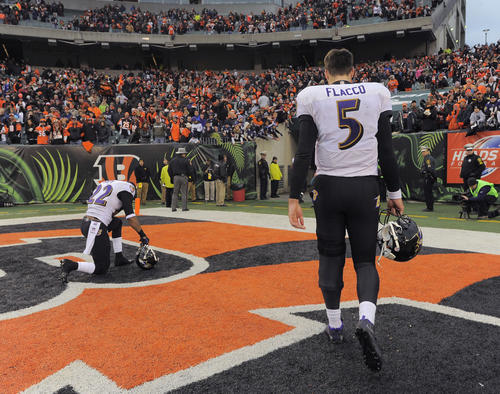Ravens quarterback Joe Flacco, right, walks to the locker room, while cornerback Jimmy Smith kneels to pray in the end zone after the 34-17 loss to the Cincinnati Bengals.