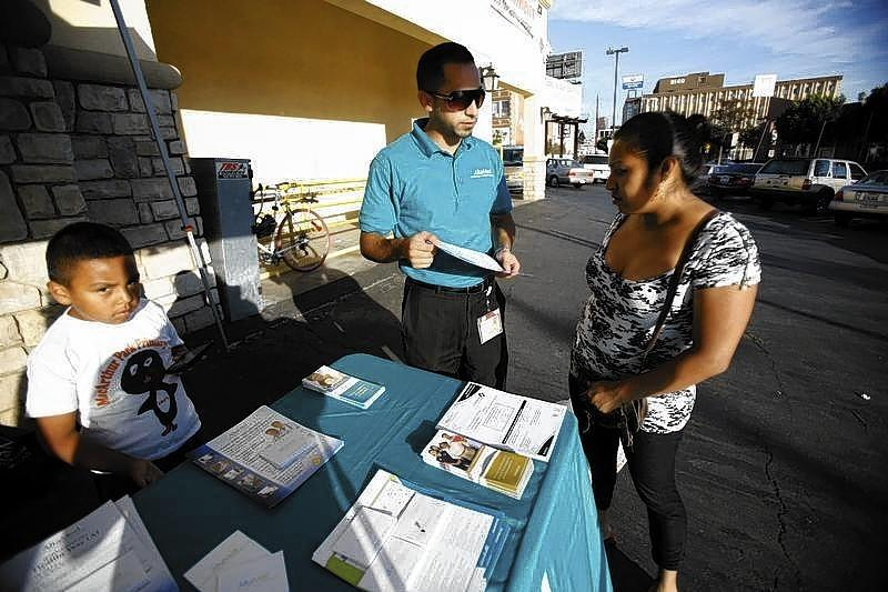 Jaime Corona, patient care coordinator at AltaMed, speaks to a woman during a community outreach on Obamacare in Los Angeles