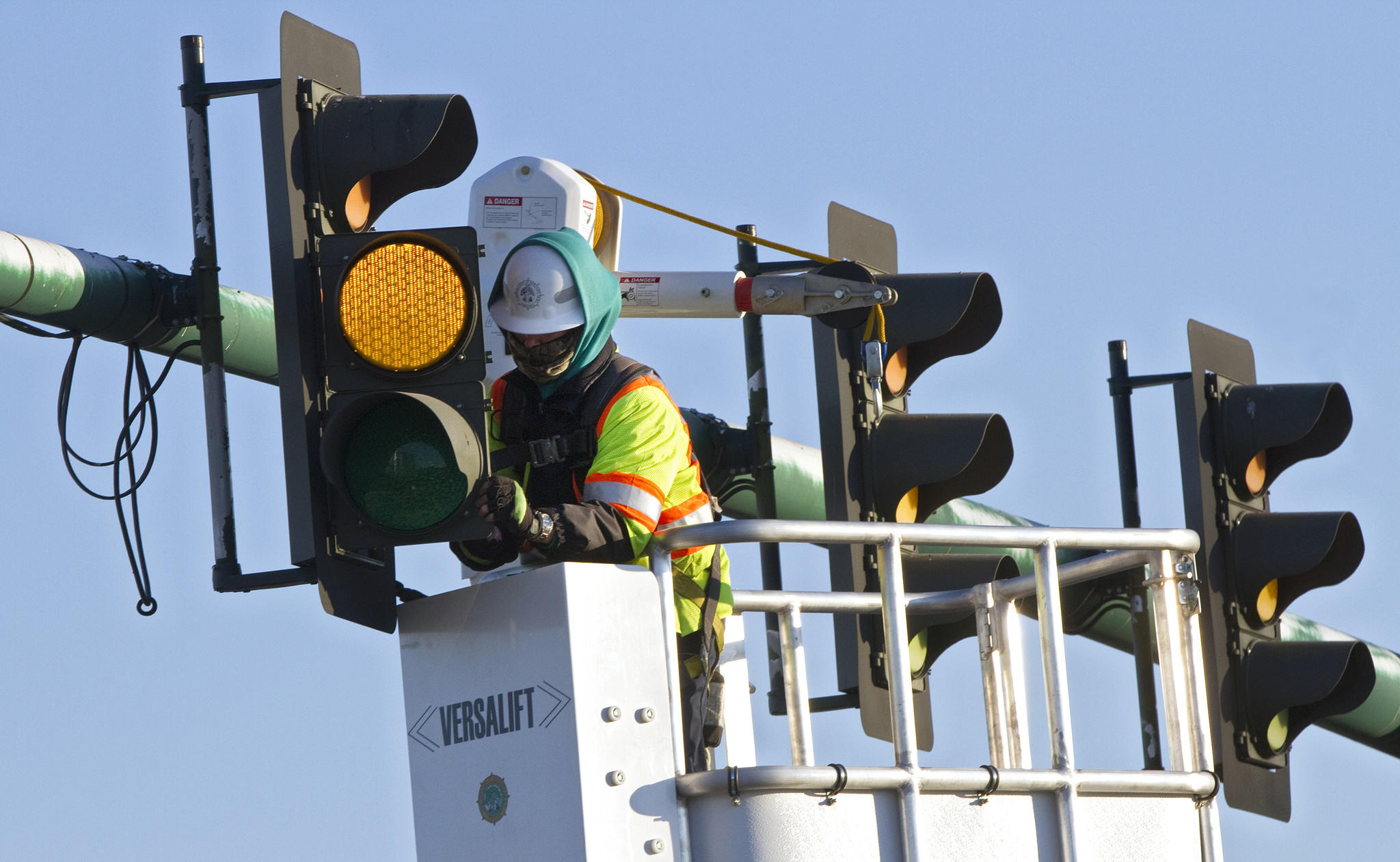 Technician Dan Bearor installs new LED lightbulbs in the traffic signals at the intersection of Jefferson Avenue and Brick Kiln Boulevard on Friday in Newport News. The city of Newport News began switching to LED units about seven years ago, and technicians are now working to replace the old lights with new ones.