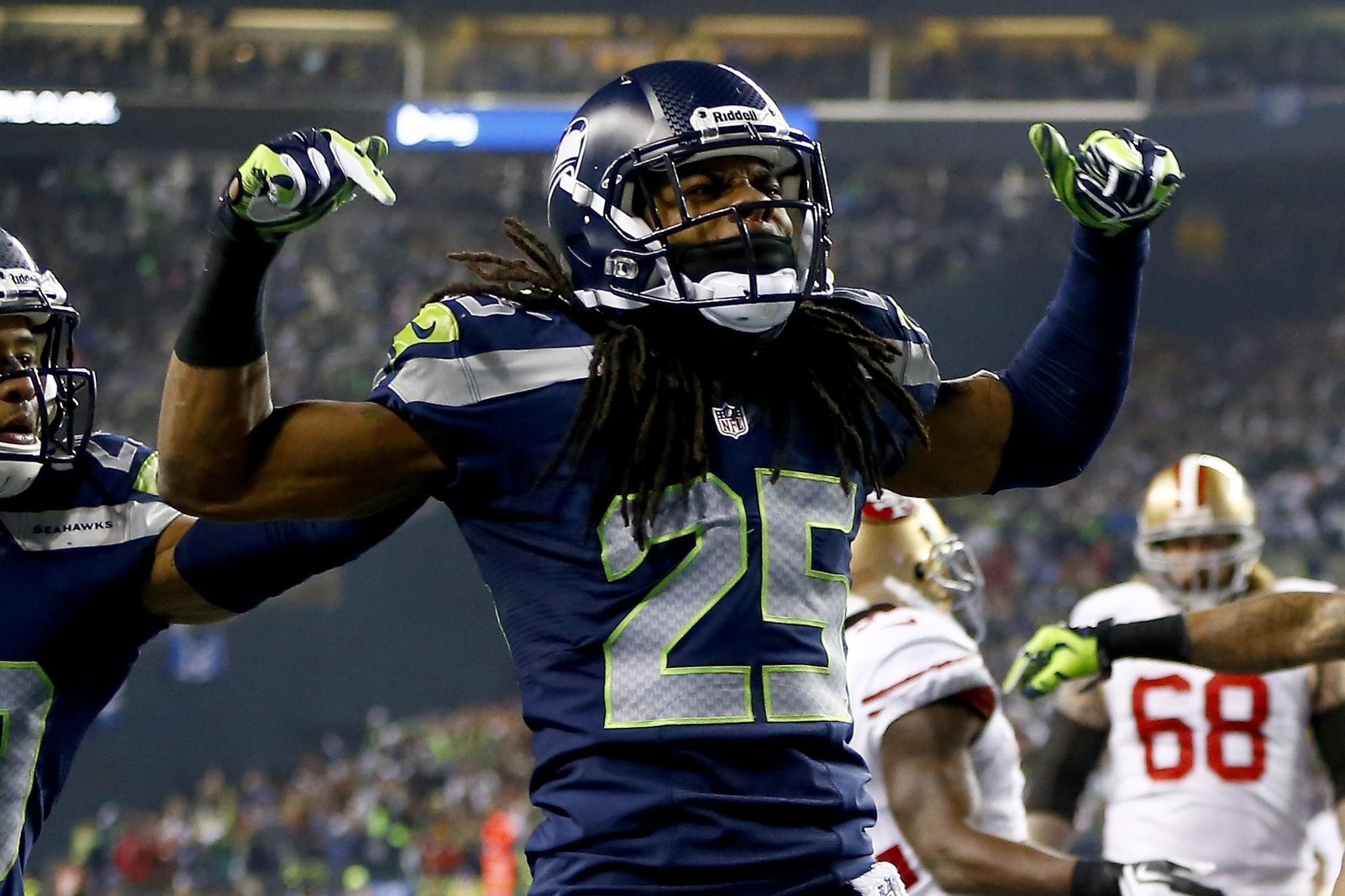 Cornerback Richard Sherman of the Seattle Seahawks celebrates after he tips the ball leading to an intereption by outside linebacker Malcolm Smith #53 to clinch the victory for the Seahawks against the San Francisco 49ers during the 2014 NFC Championship at CenturyLink Field.