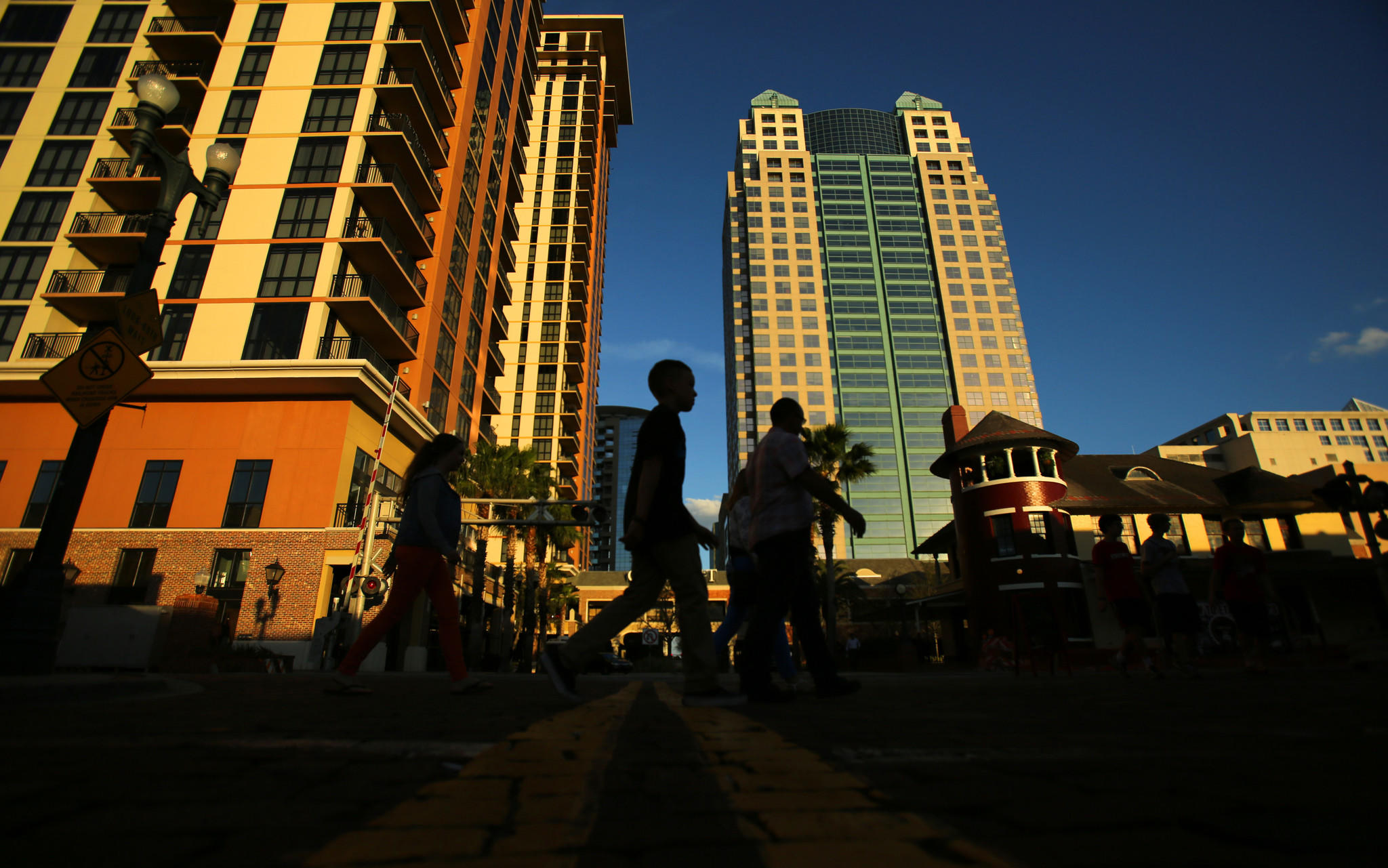 Pedestrians walk through downtown as the sun sets on the Orlando skyline on Wednesday, January 16, 2013.