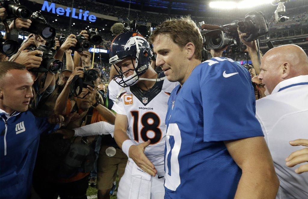 Peyton and Eli Manning walk off the field after a game in September.
