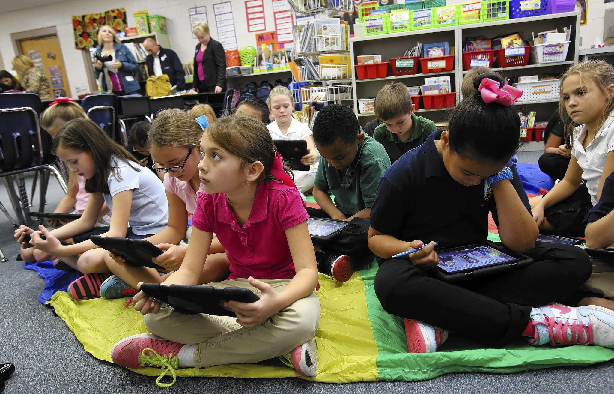 Florida Education Commissioner Pam Stewart reads as Lost Lake Elementary school students follow along on their iPads, on Wednesday, January 22, 2014, during a program to celebrate the school's literacy celebration.