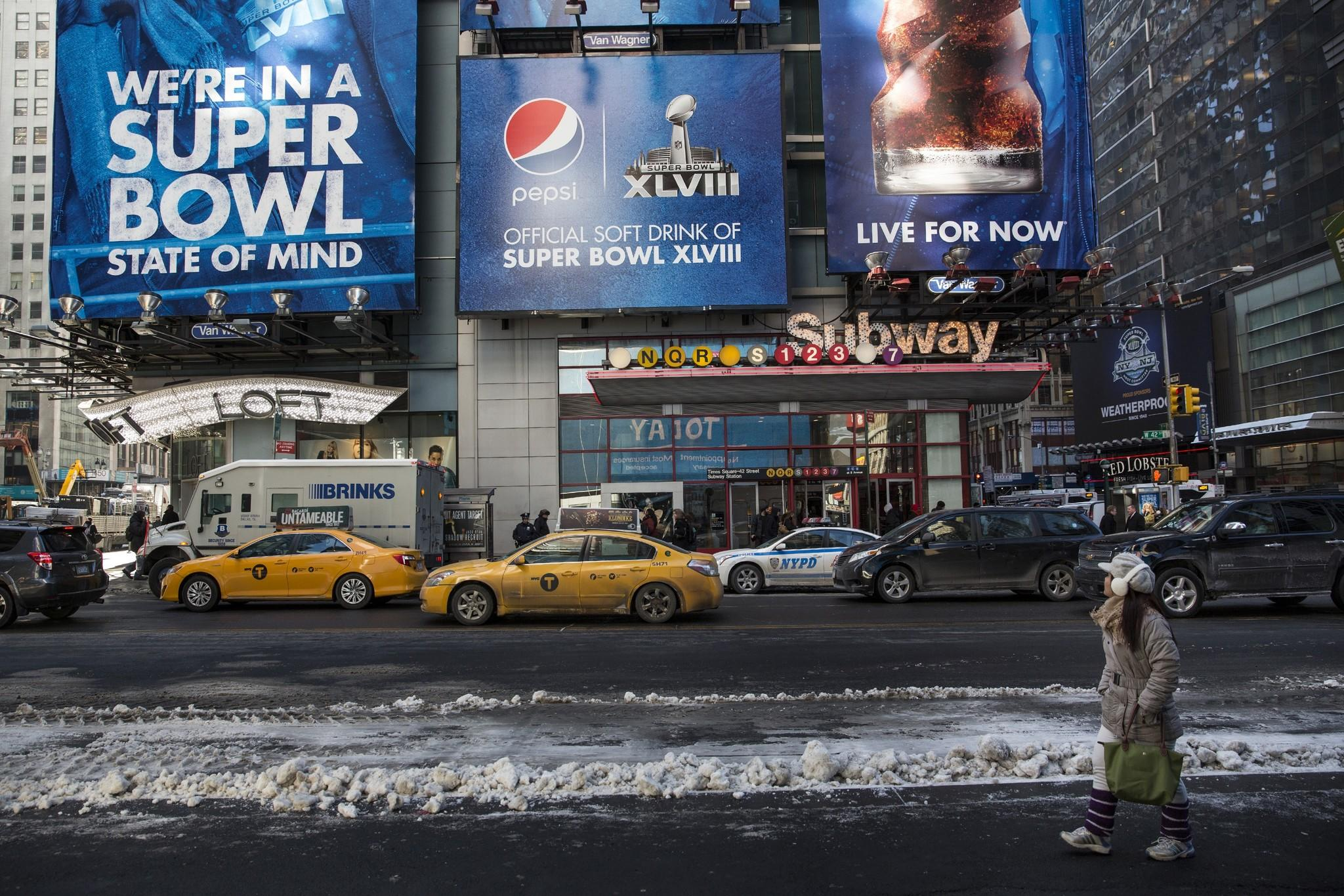"NEW YORK, NY - JANUARY 24: A woman walks past an advertisement referencing Super Bowl XLVIII, which will be played in East Rutherford, NJ in two weekends, on January 24, 2014 in Times Square in New York City. In preperation for the Super Bowl, New York City is turning sections of Times Square and Broadway into ""Super Bowl Boulevard,"" which will feature events such as games, concerts and a toboggan run."