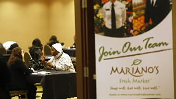 Mary Goodson, center, interviews with Christa Berrolini, left, a recruiting manager with Mariano's, during an initial screening interview at a job fair for potential employees to work at Mariano's grocery stores at the Crowne Plaza Chicago Metro in Chicago on Tuesday, Dec. 12, 2013.