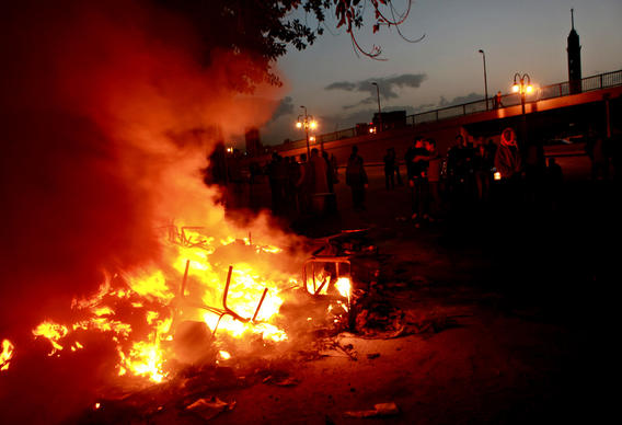 Men add fuel to the fire burning in front of ruling party headquarters in Tahrir Square, where protests continued into the night.