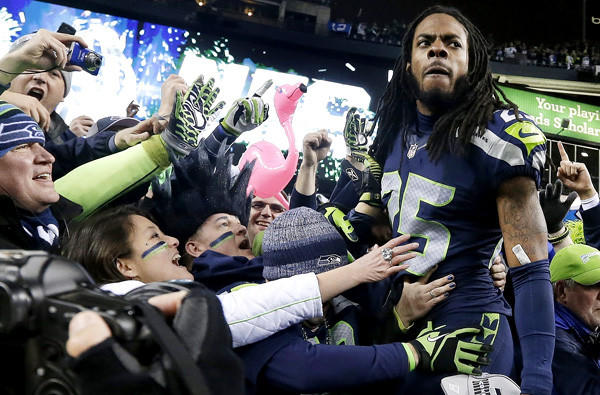 Seahawks cornerback Richard Sherman celebrates with fans after after winning the NFC championship game on Sunday in Seattle.