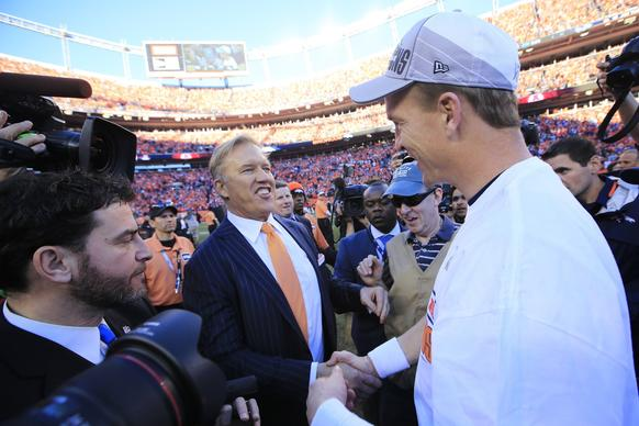 Broncos quarterback Peyton Manning is congratulated by John Elway, a two-time Super Bowl winner and current president of football operations for Denver, after a 26-16 victory over the New England Patriots on Sunday in the AFC championship game.