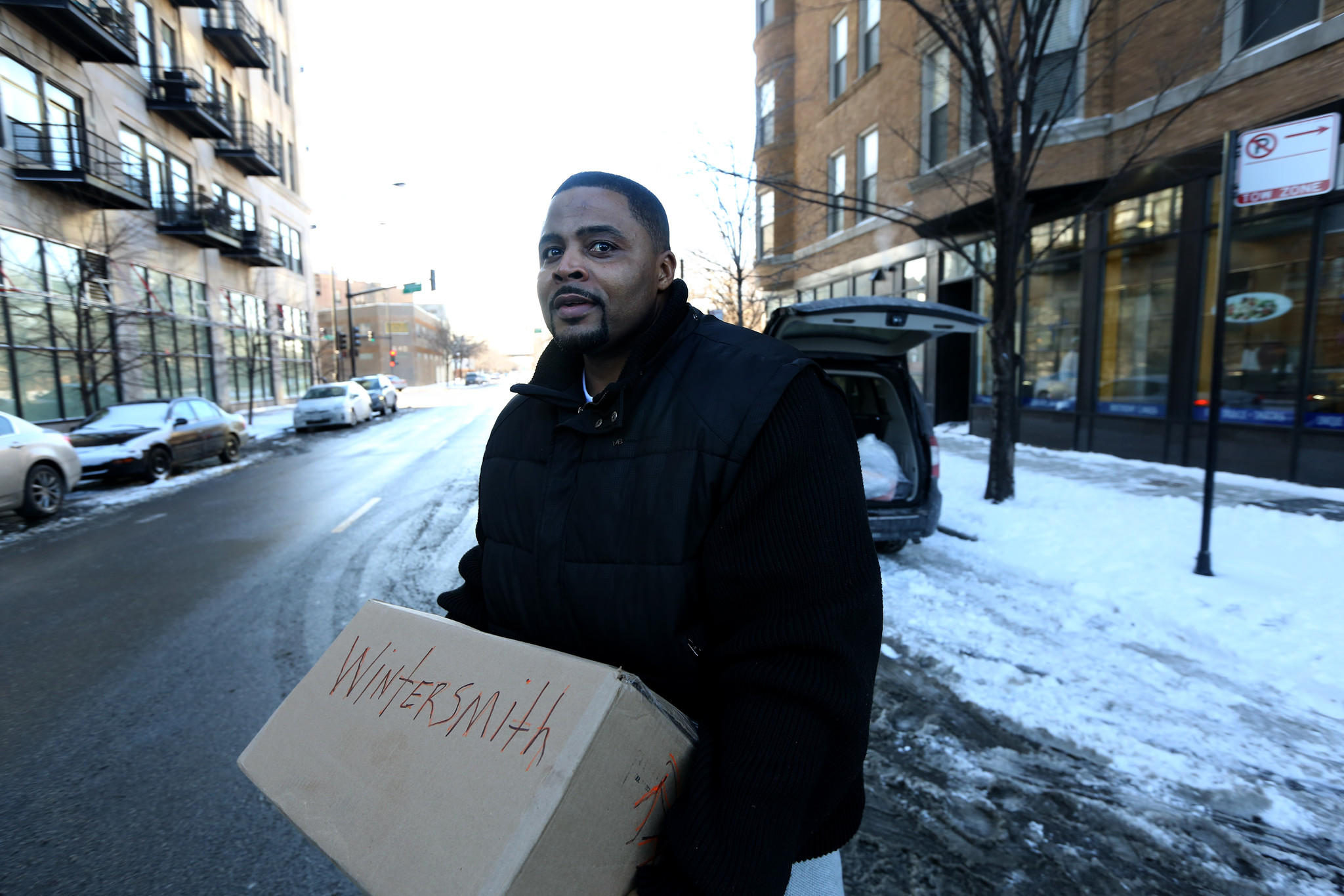 On the day he was released from prison, Reynolds Wintersmith carries a box of donated clothes on Tuesday Jan. 21, 2014 into the halfway house in Chicago where he will live for the next couple months.