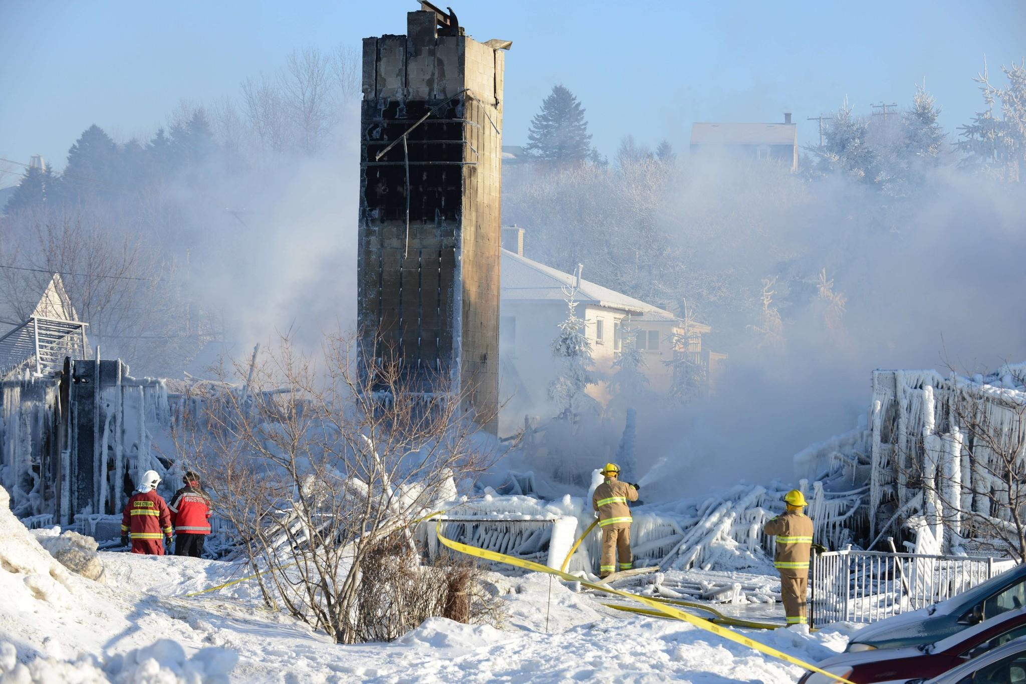 Canadian firefighters douse the burnt remains of a retirement home in L'Isle-Verte on January 23, 2014.