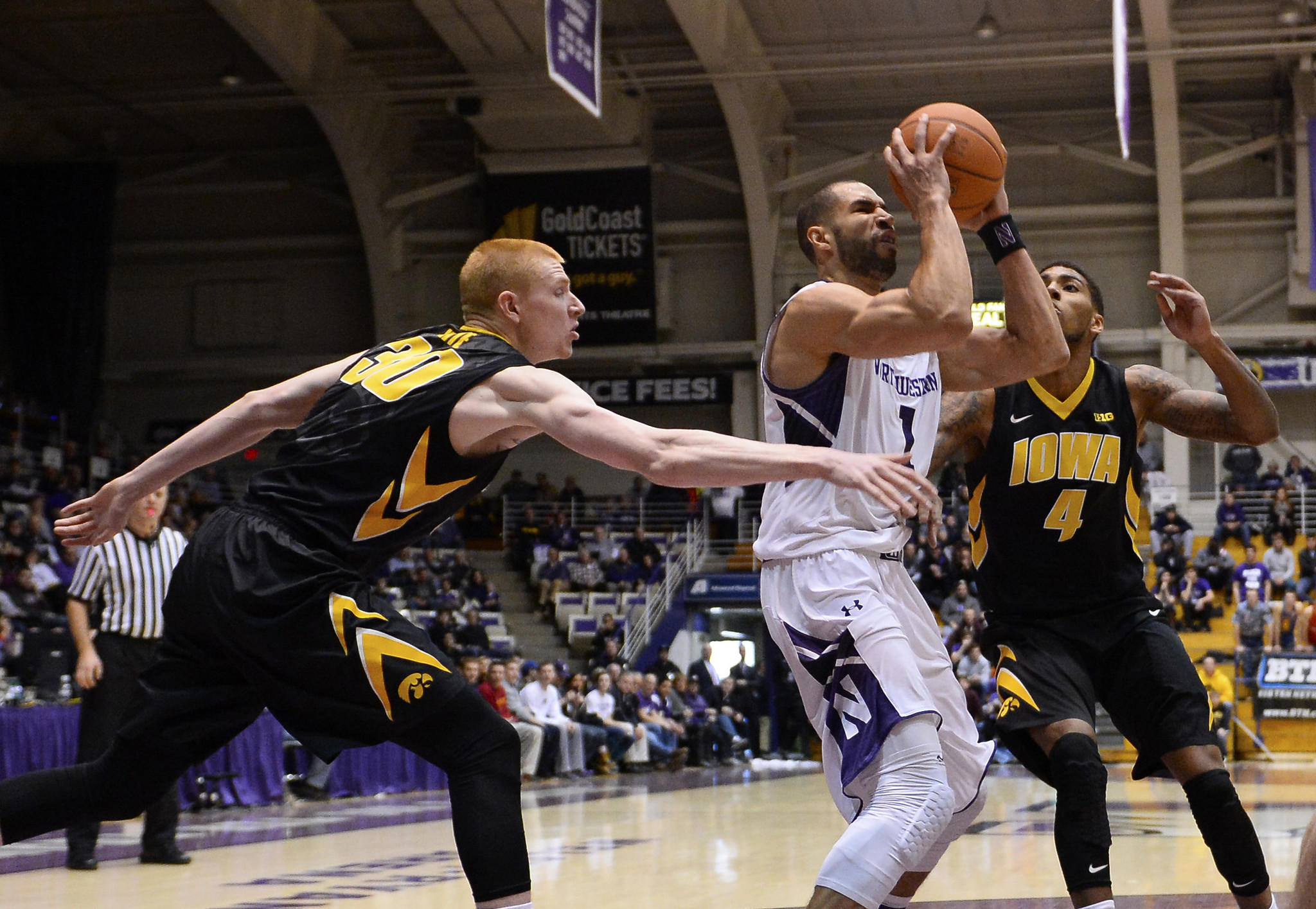 Northwestern guard Drew Crawford shoots against Iowa forward Aaron White (30) and guard Roy Devyn Marble (4) during the first half at Welsh-Ryan Arena.