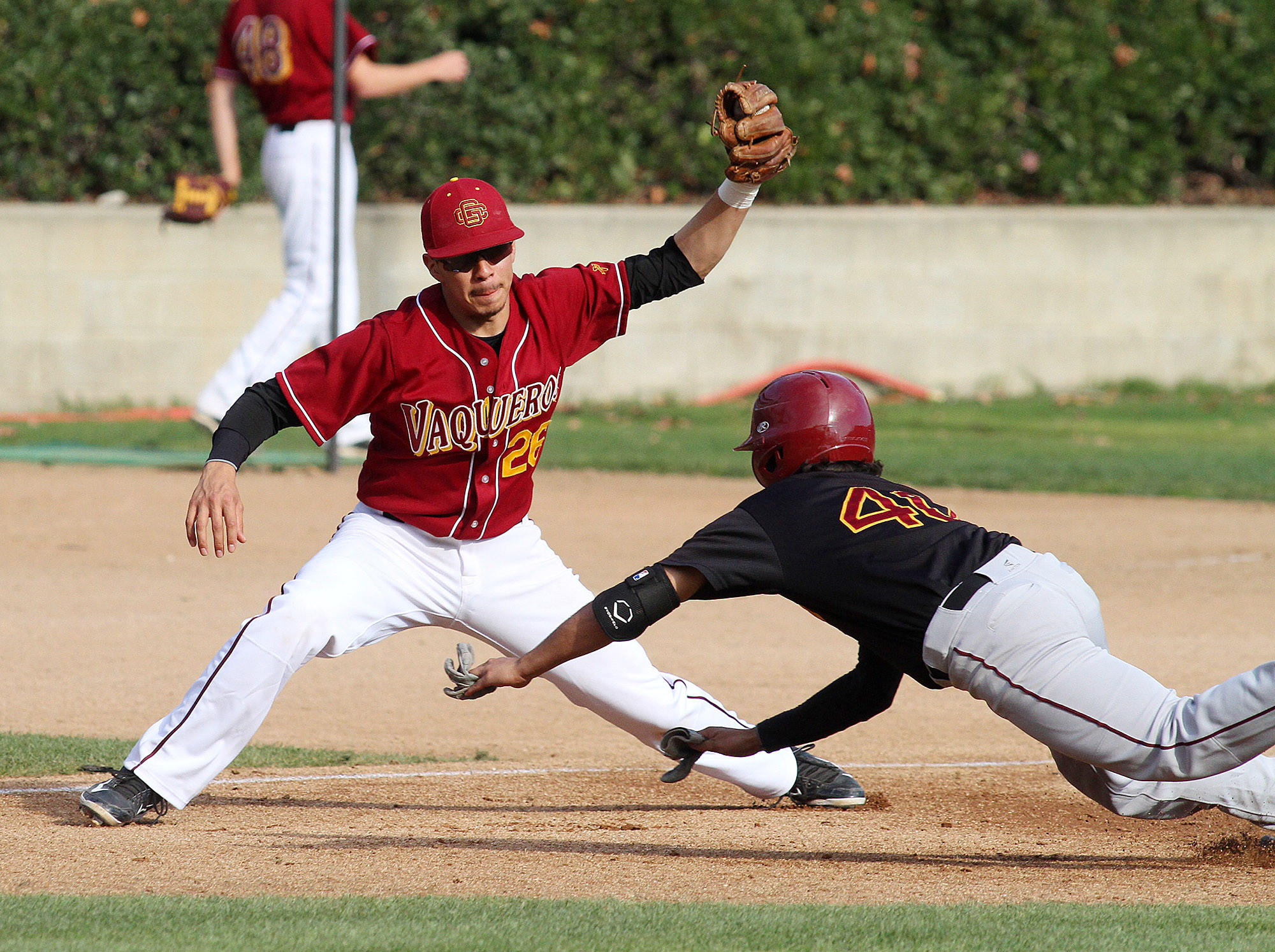 GCC third baseman Randy Medellin catches the ball and tags out Lino Lares at third base in a scrimmage against the other half of the GCC team at Stengel Field in Glendale on Wednesday, January 22, 2014.