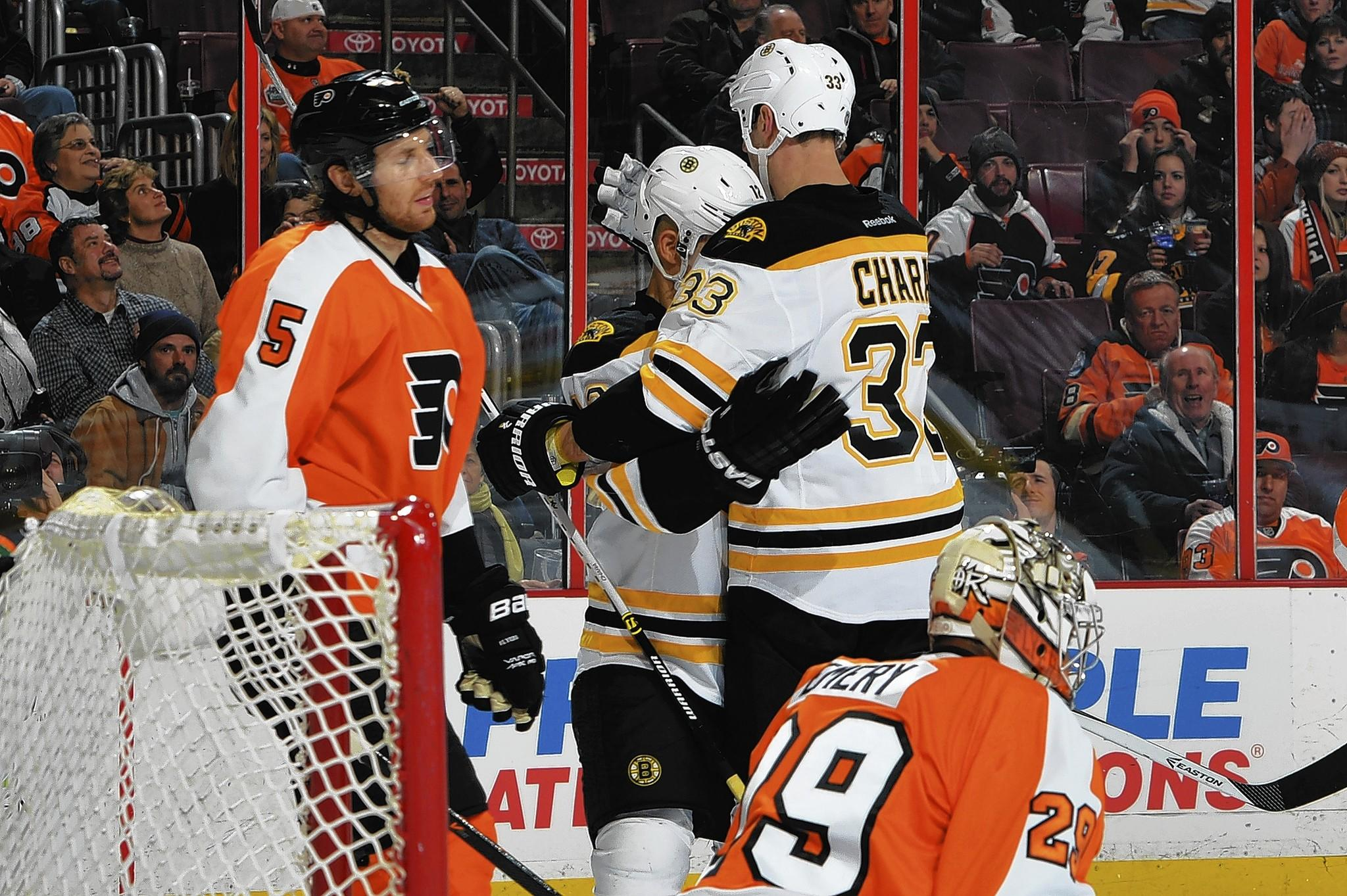 Jarome Iginla #12 and Zdeno Chara #33 of the Boston Bruins celebrate a third period goal as Braydon Coburn #5 and Ray Emery #29 of the Philadelphia Flyers react at the Wells Fargo Center on January 25, 2014 in Philadelphia, Pennsylvania.