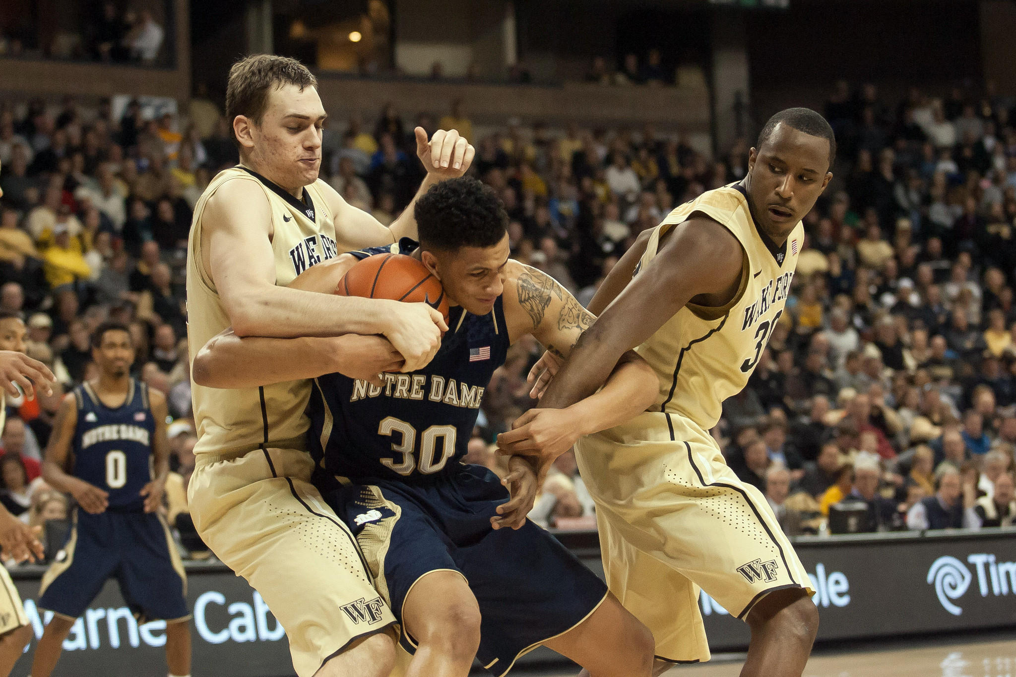 Notre Dame forward Zach Auguste (30) fights for a ball between Wake Forest forward Tyler Cavanaugh (34) and forward Travis McKie (30) during the second half.