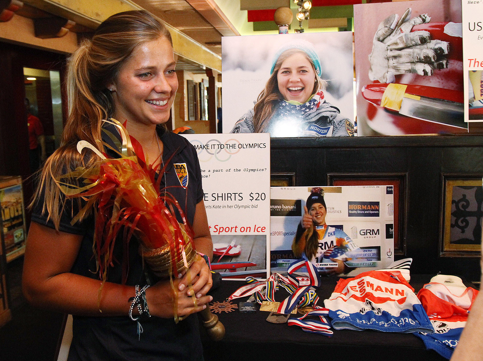 File Photo: Kate Hansen, a La Cañada High School graduate, holds an Olympic torch decoration from the 1984 Olympics for a photo at Los Gringos Locos for a fundraiser to help raise money for her to train with the USA Women's Olympic Luge Team in August 2013. Hansen slid to a victory in women's single luge on Saturday, Jan. 25, 2014.