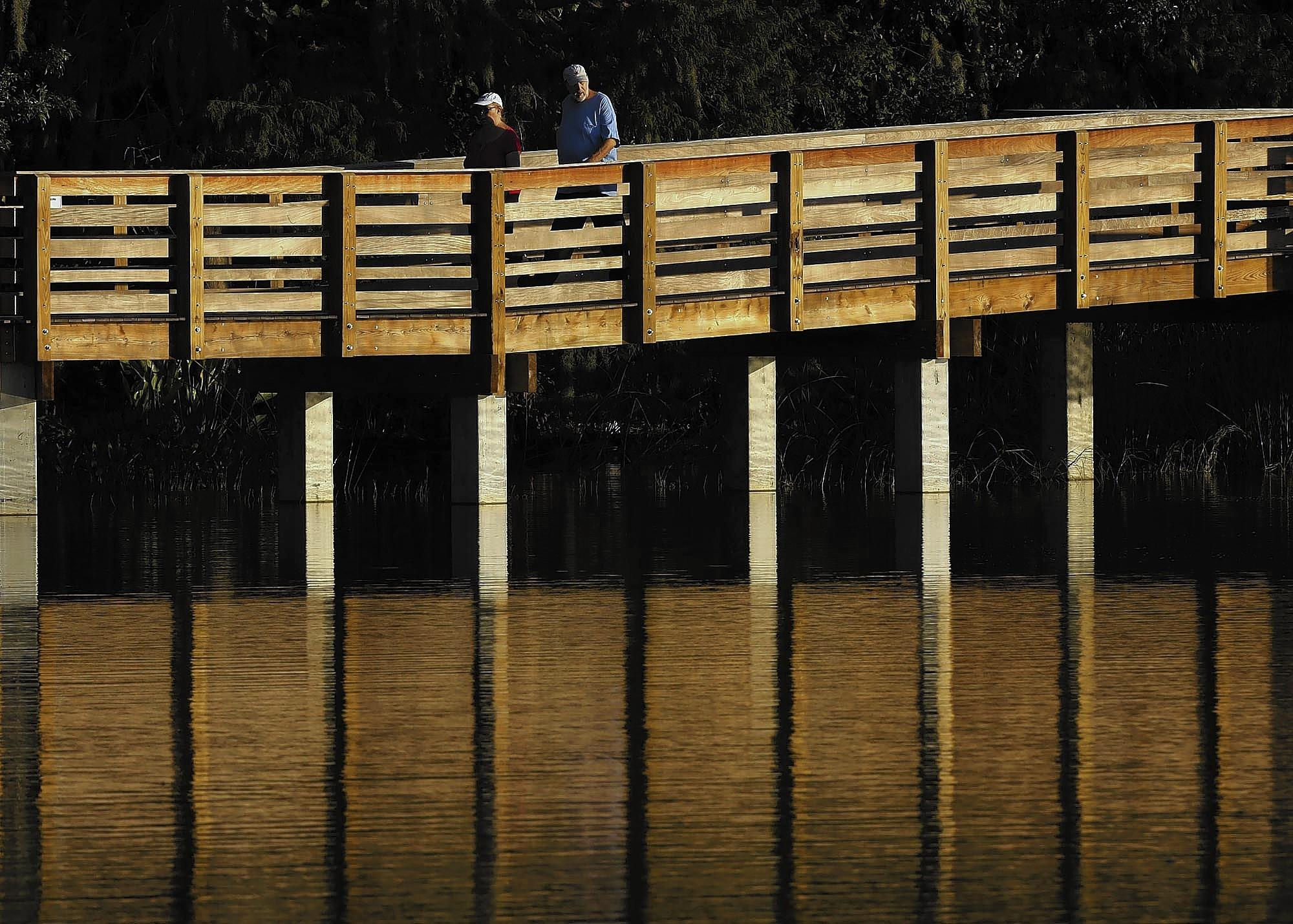 Walkers enjoy the newly rebuilt boardwalk at Lake Dora in Mount Dora on Wednesday, October 2, 2013. (Stephen M. Dowell/Orlando Sentinel)