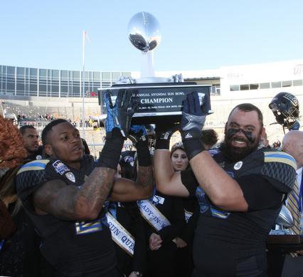 Safety Brandon Sermons, left, and Y back Jordan Barrett raise the Sun Bowl trophy after a 42-12 victory over Virginia Tech on Tuesday in El Paso, Texas.