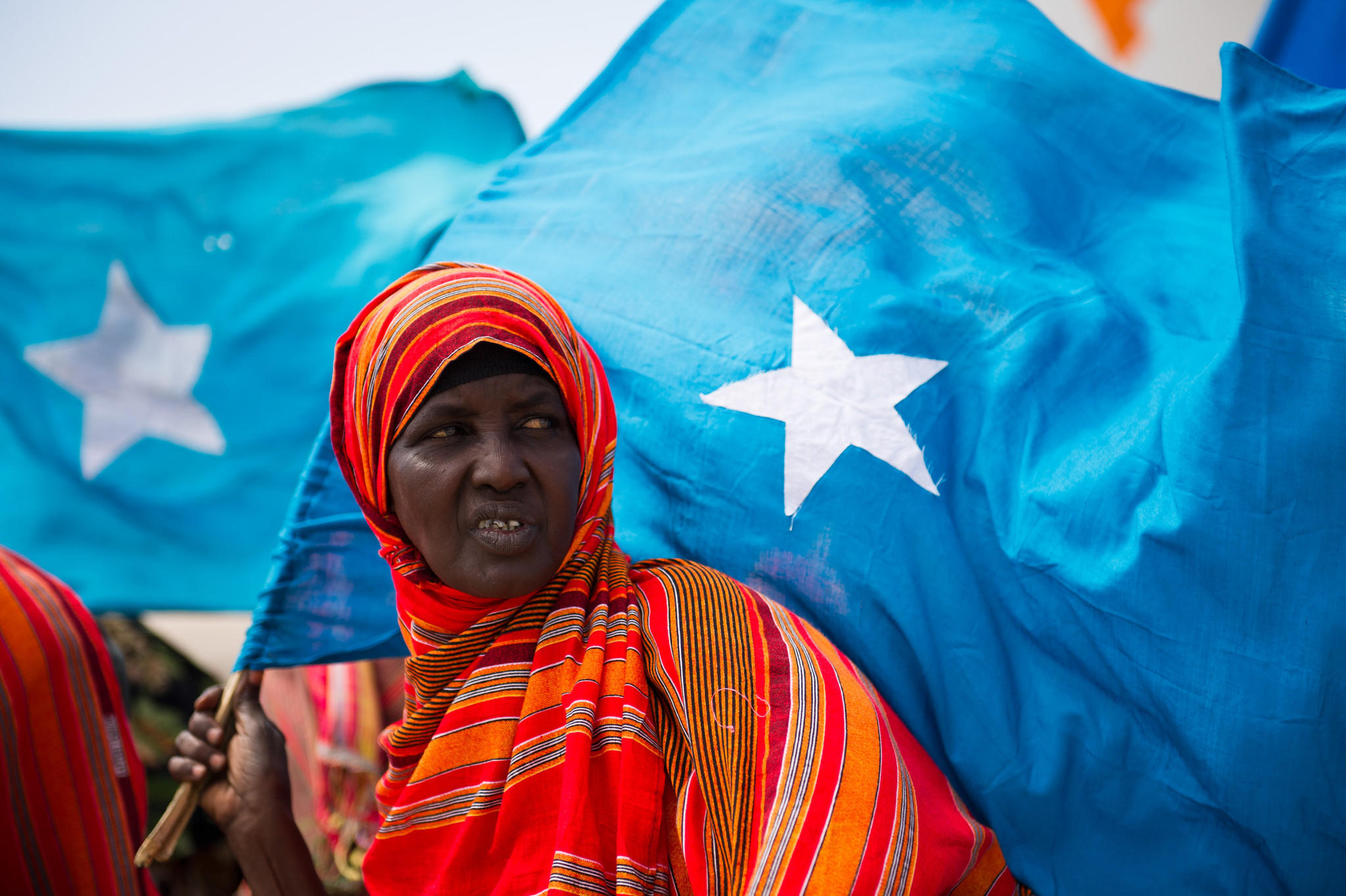 A woman stands holding the Somali flag.