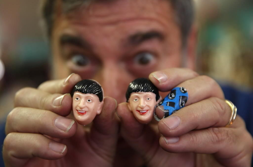 Ted Frankel, owner of Uncle Fun, holds up two Beatle heads on Jan. 8.