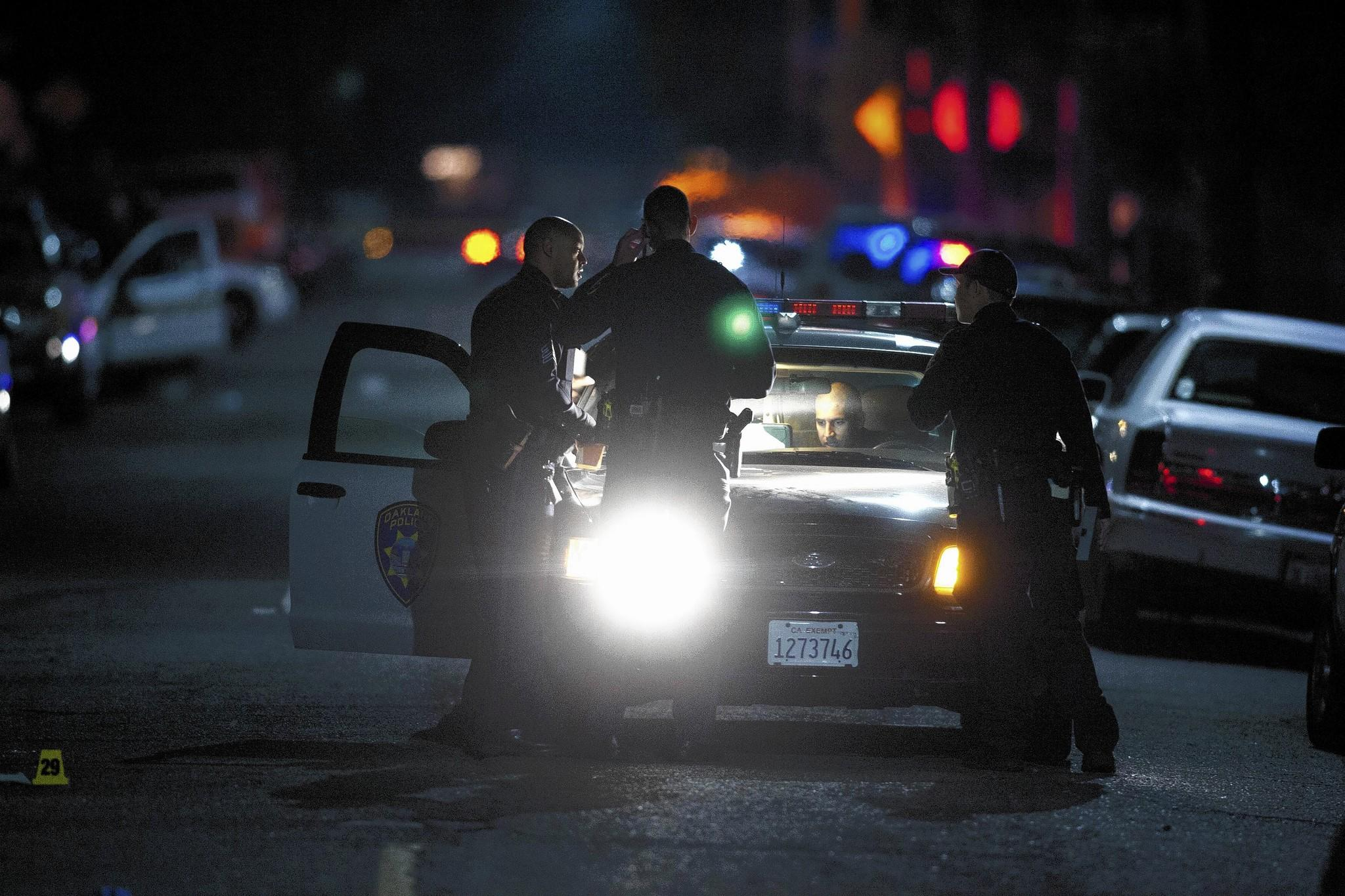 Oakland police gather evidence at the scene of a multiple shooting in November. It is not entirely clear what spurred the city's drop in violent crime, but interviews with police, city officials and community leaders suggest that a crackdown on two of Oakland's most violent gangs helped curtail not only the murder rate but also robberies.
