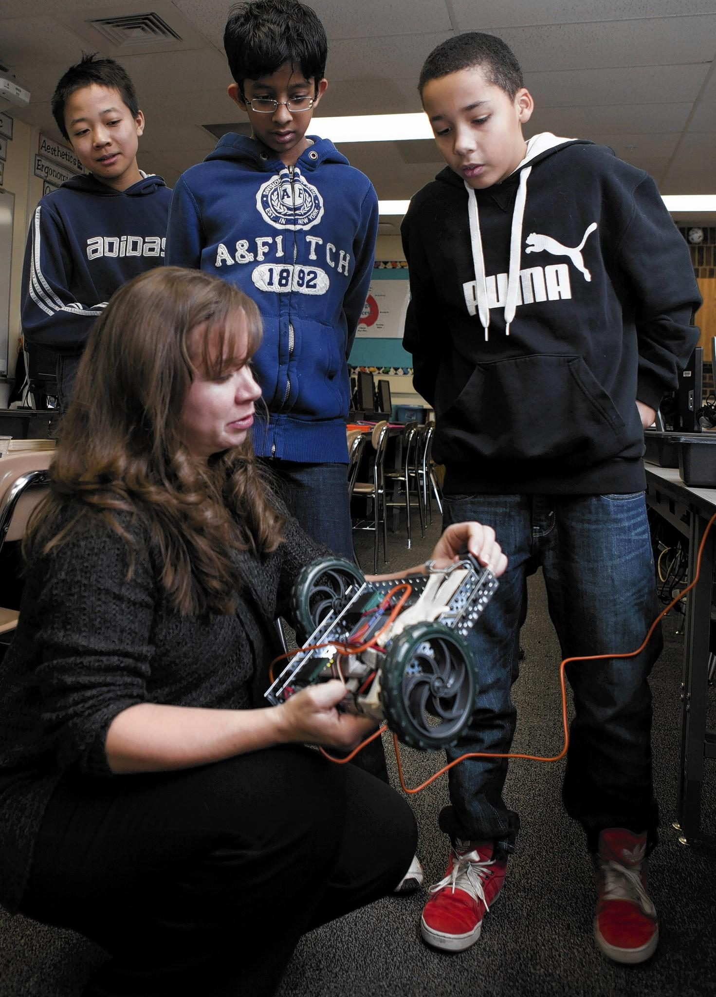Teacher Michelle Burke works with students Ken Oishi, left, Karthik Myneni and Ian Klocko at Jane Adams Jr. High School in Schaumburg.