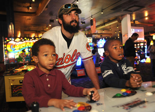 Orioles right fielder Nick Markakis, center, coaches Kevron Craig, 6, left, and Jalen Hawkins, 5, right, on how to play a football video game during the 35th annual OriolesREACH Holiday Party for Kids at Dave & Buster's at Arundel Mills.