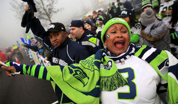 Marcia Shiri-Wasto and other Seahawks fans line the streets of Seattle on Sunday to cheer the team on its way to the airport to depart for Super Bowl XLVIII.