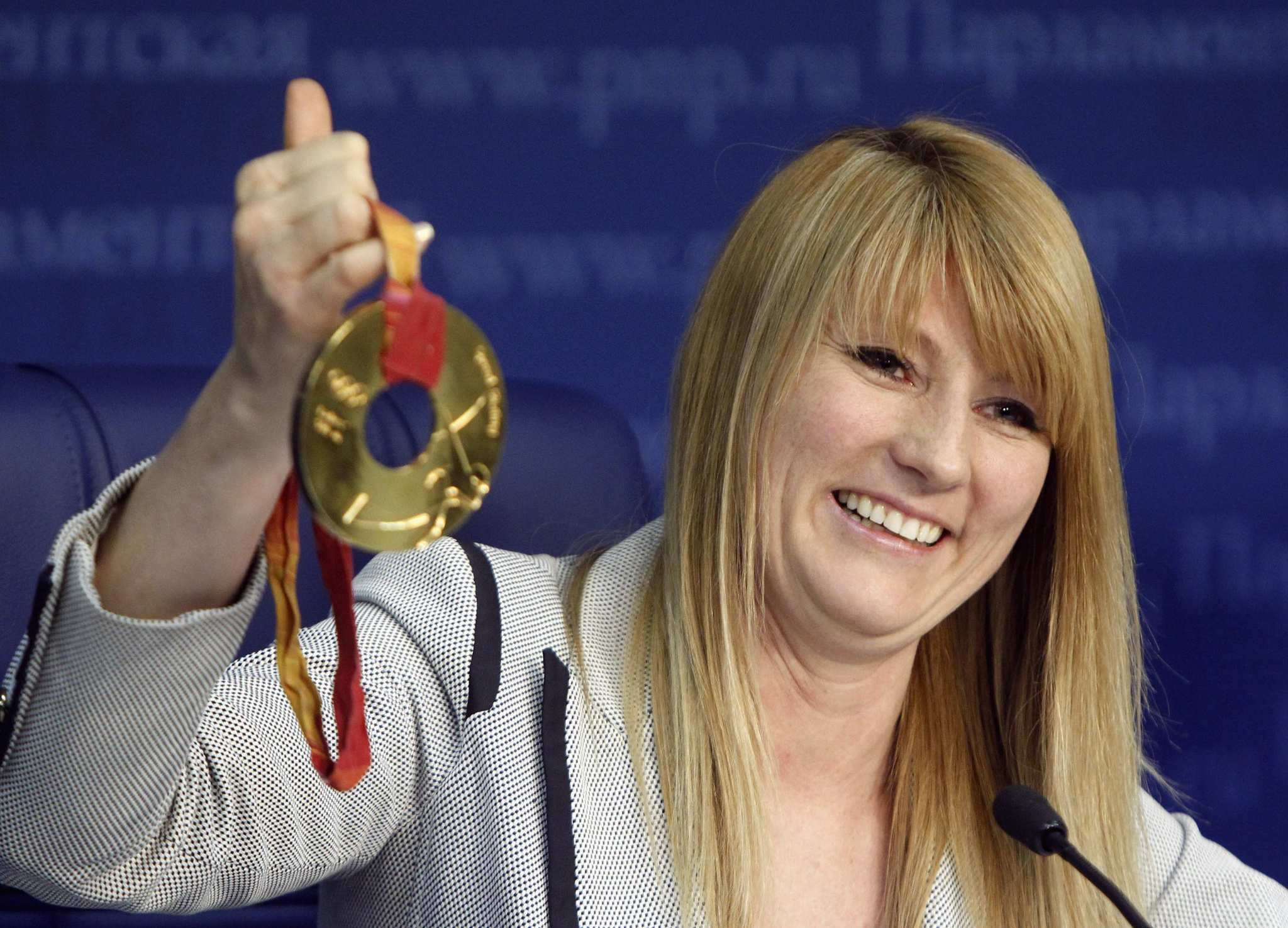 Svetlana Zhurova, a former Russian speed skater and 'mayor' of Sochi's Olympic Village, shows her Olympic medal during a news conference.