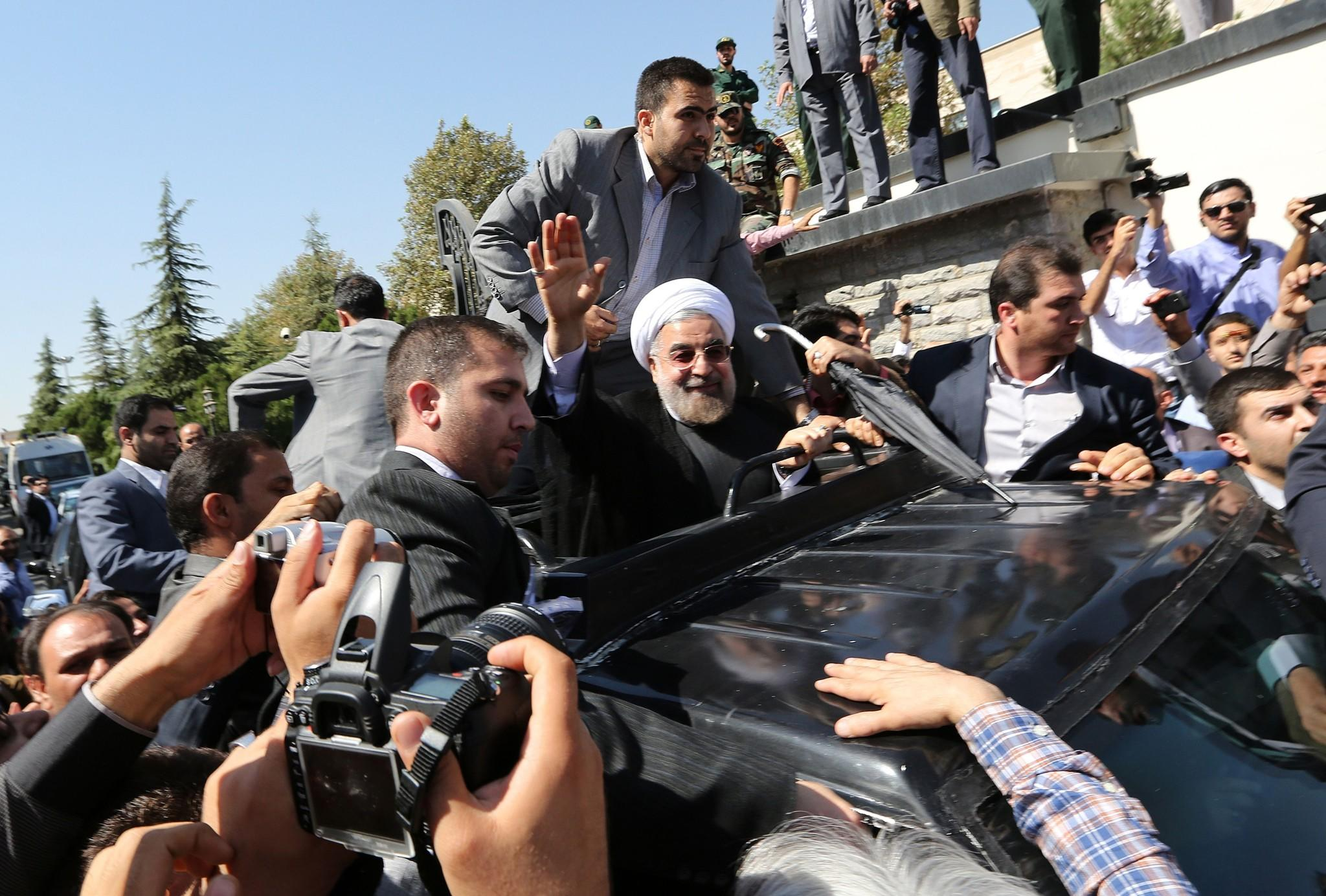 Iranian president Hassan Rouhani waves to journalists and supporters upon his return to Tehran from New York in September.