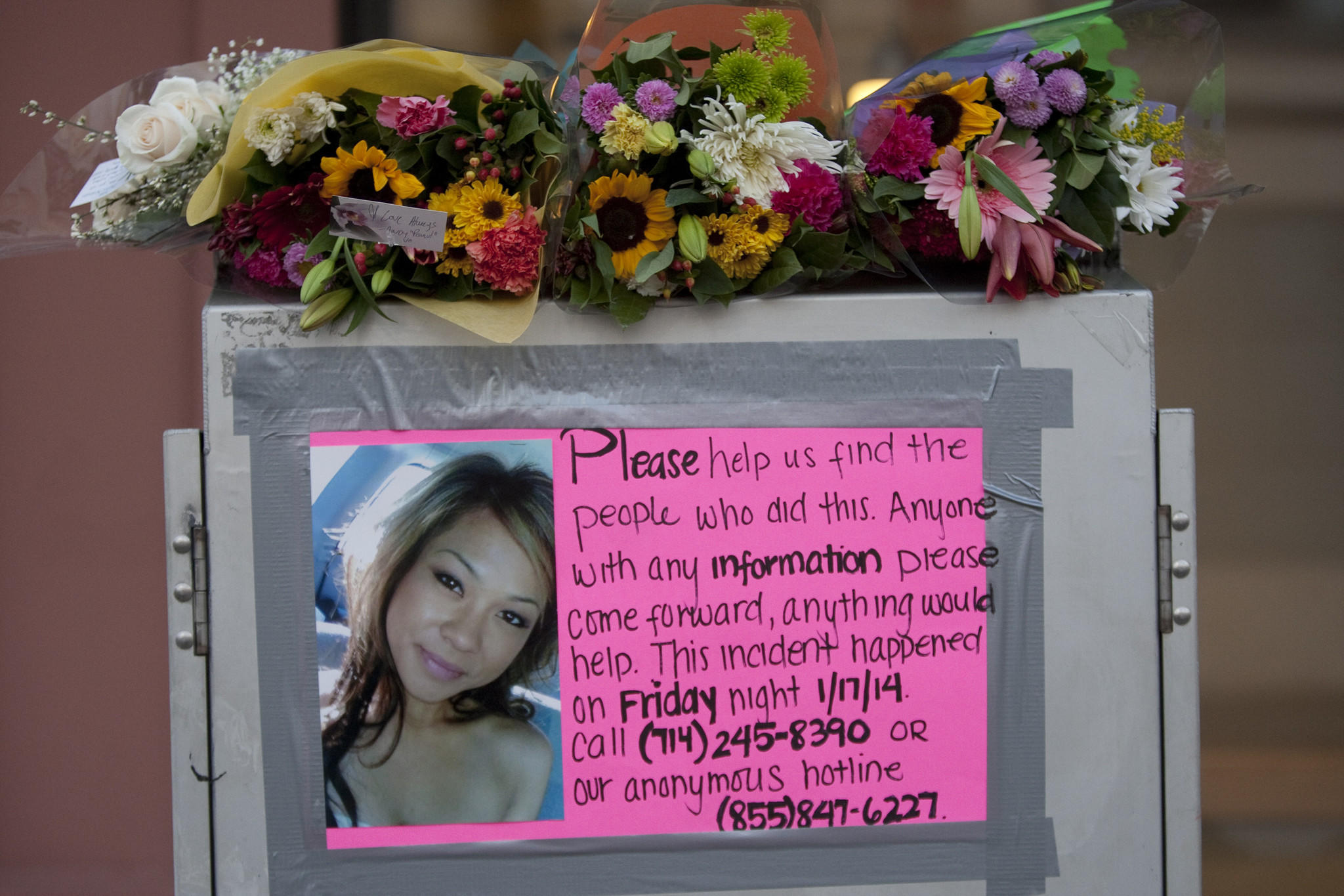 A poster seeking information is displayed at a memorial for Kim Pham, the 23-year-old woman who died after being attacked by a group of people outside a Santa Ana nightclub.