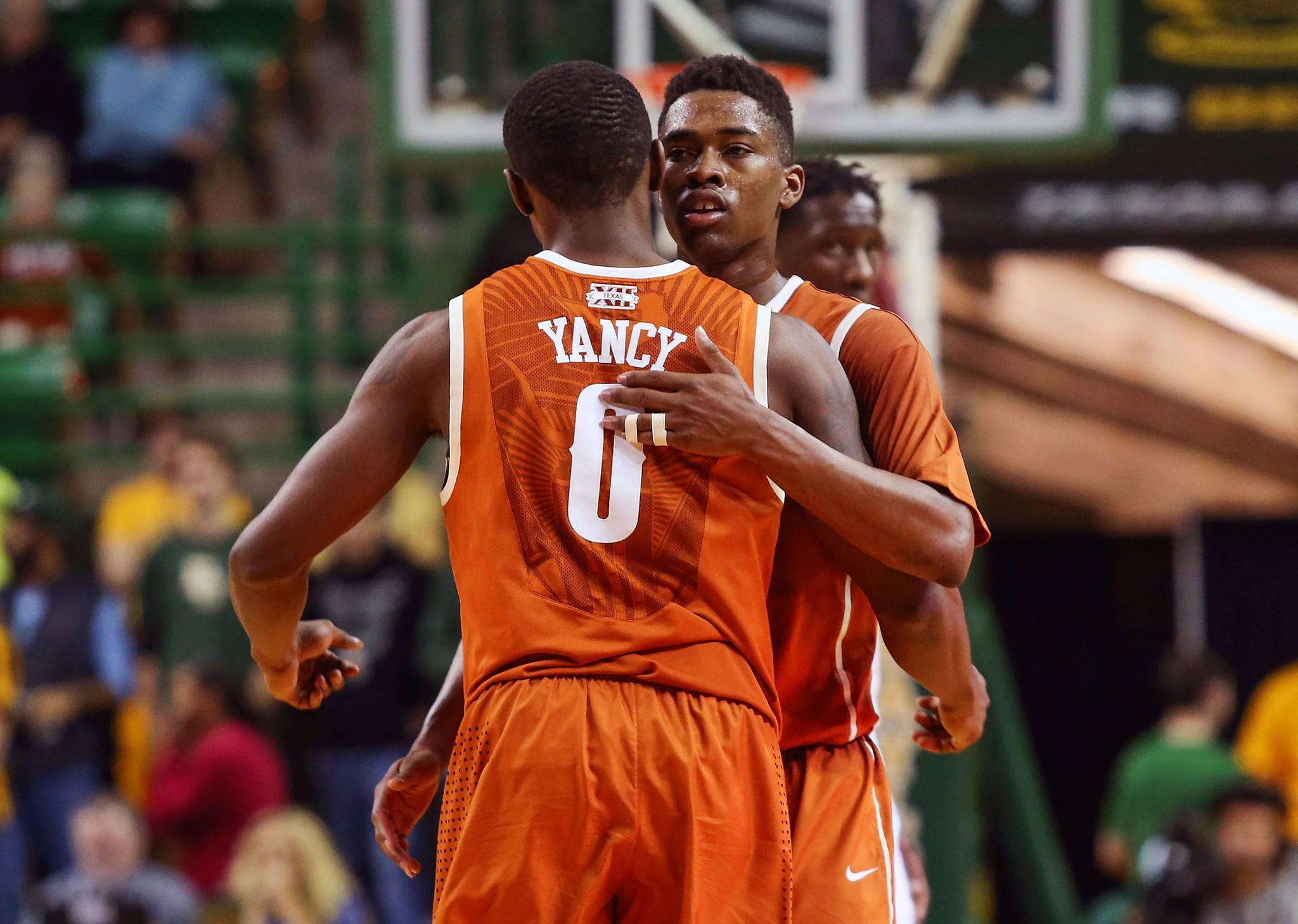 Longhorns guard Isaiah Taylor (1) hugs guard Kendal Yancy (0) during the second half against Baylor at The Ferrell Center.