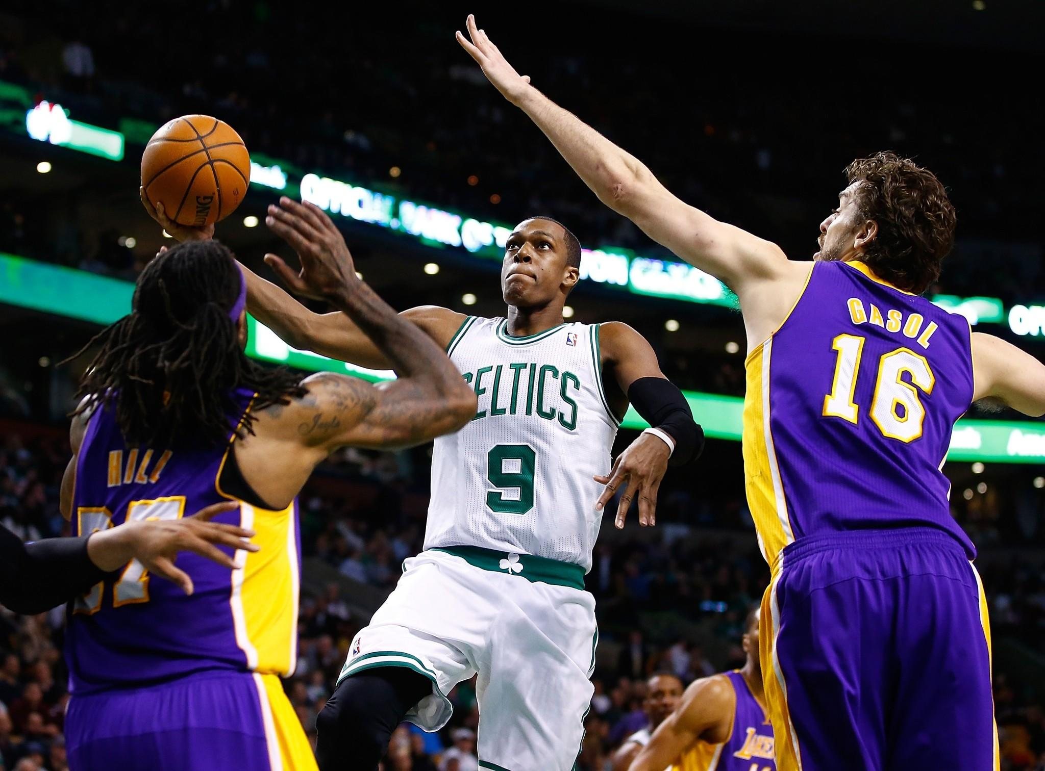 Celtics point guard Rajon Rondo takes the ball to the basket against Lakers big men Pau Gasol and Jordan Hill during a game earlier this season. Rondo and Celtics are in the draft lottery hunt with the Lakers.