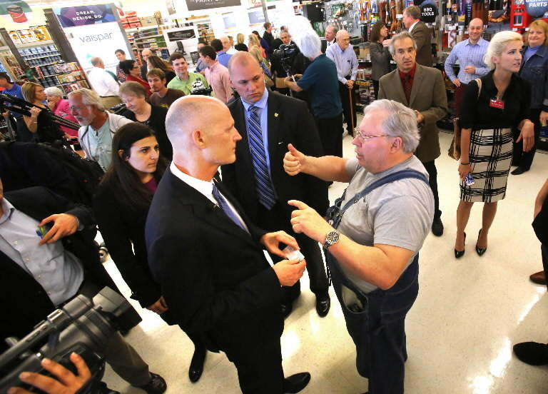 Gov. Rick Scott listens to Ace Hardware shopper Larry Hoedl during Scott's visit in Orlando, Tuesday, Jan. 28, 2014. Scott was promoting his proposed tax cuts in the upcoming state budget.