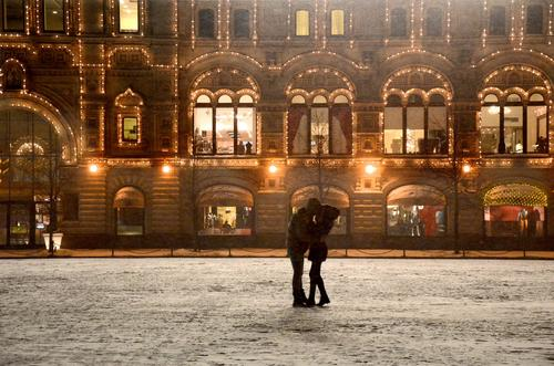 A couple embraces outside GUM, an arcade-style, three-level shopping center on Red Square that is housed in an 1890s structure.