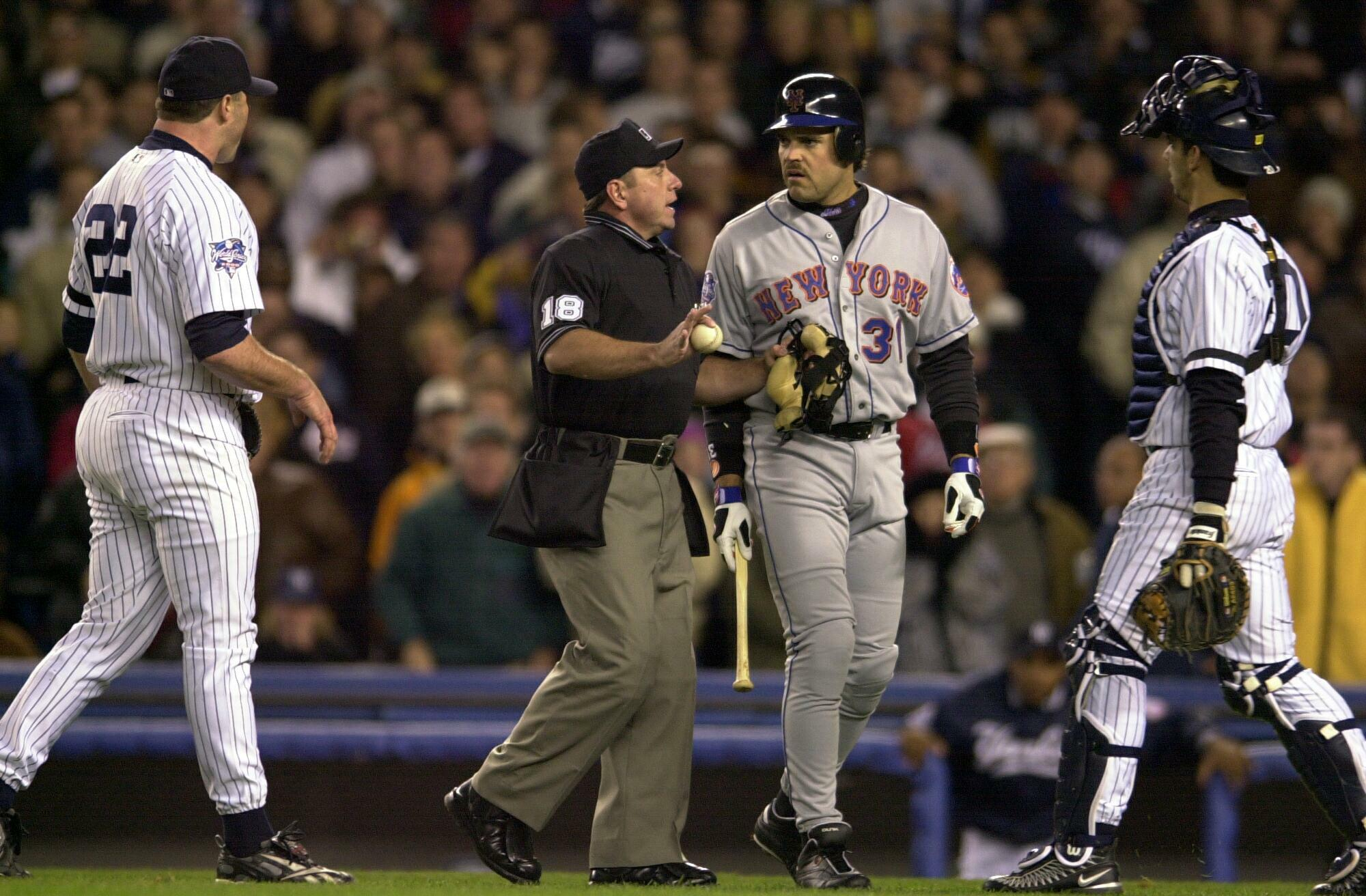 The New York Mets' Mike Piazza and the New York Yankees' Roger Clemens exchange words after Clemens threw a piece of broken bat back at Piazza in the first inning of Game 2 of the 2000 World Series at Yankee Stadium.