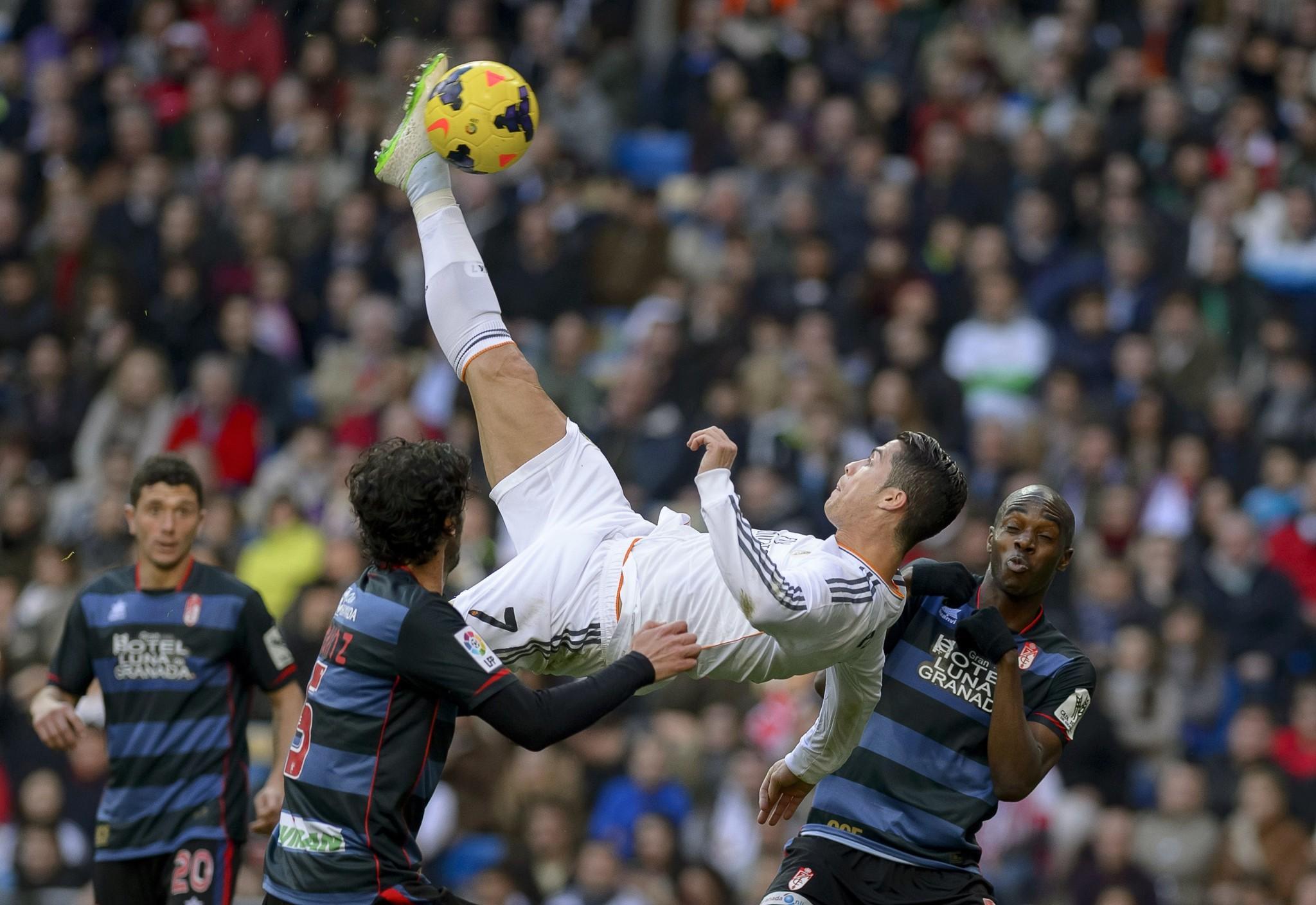 TOPSHOTS Real Madrid's Portuguese forward Cristiano Ronaldo (C) kicks the ball during the Spanish league football match Real Madrid vs FC Granada at the Santiago Bernabeu stadium in Madrid on January 25, 2014.