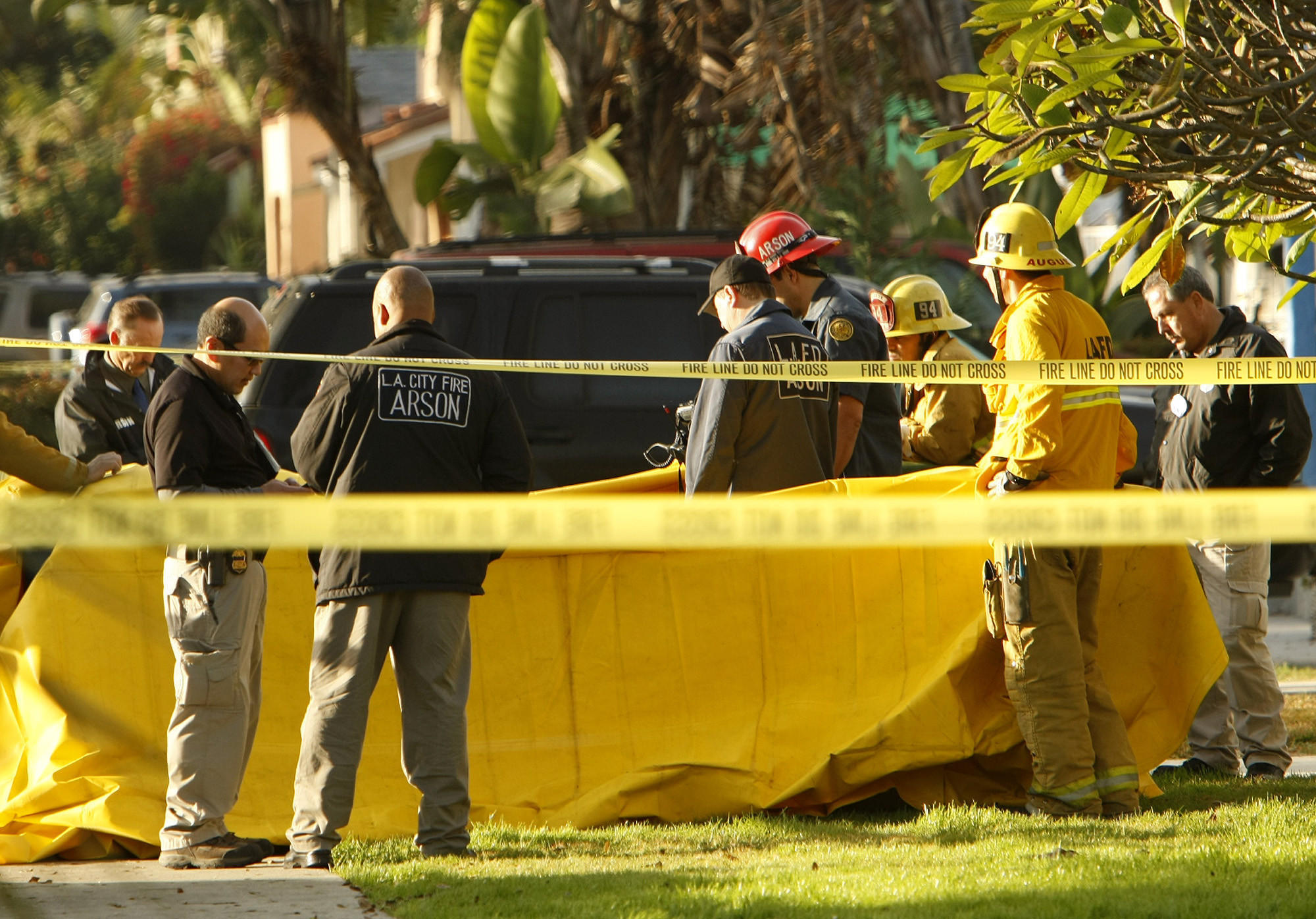 Investigators at the site of a house fire Tuesday in Mid-City that left a man dead.