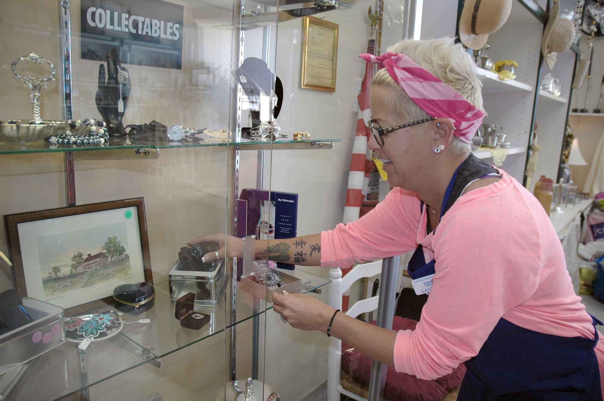 La Providencia Guild member Sandra Kelley arranges the jewelry in the new glass display case at the thrift shop at 3301 W. Burbank Blvd.